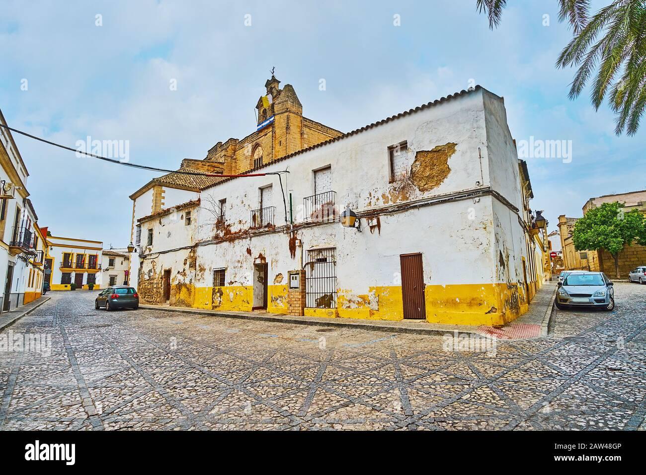 Edificio abandonado en mal estado en la calle Alegria del casco antiguo con vistas al campanario de la iglesia medieval de San Mateo (San Mateo) sobre el fondo, Jerez, Sp Foto de stock