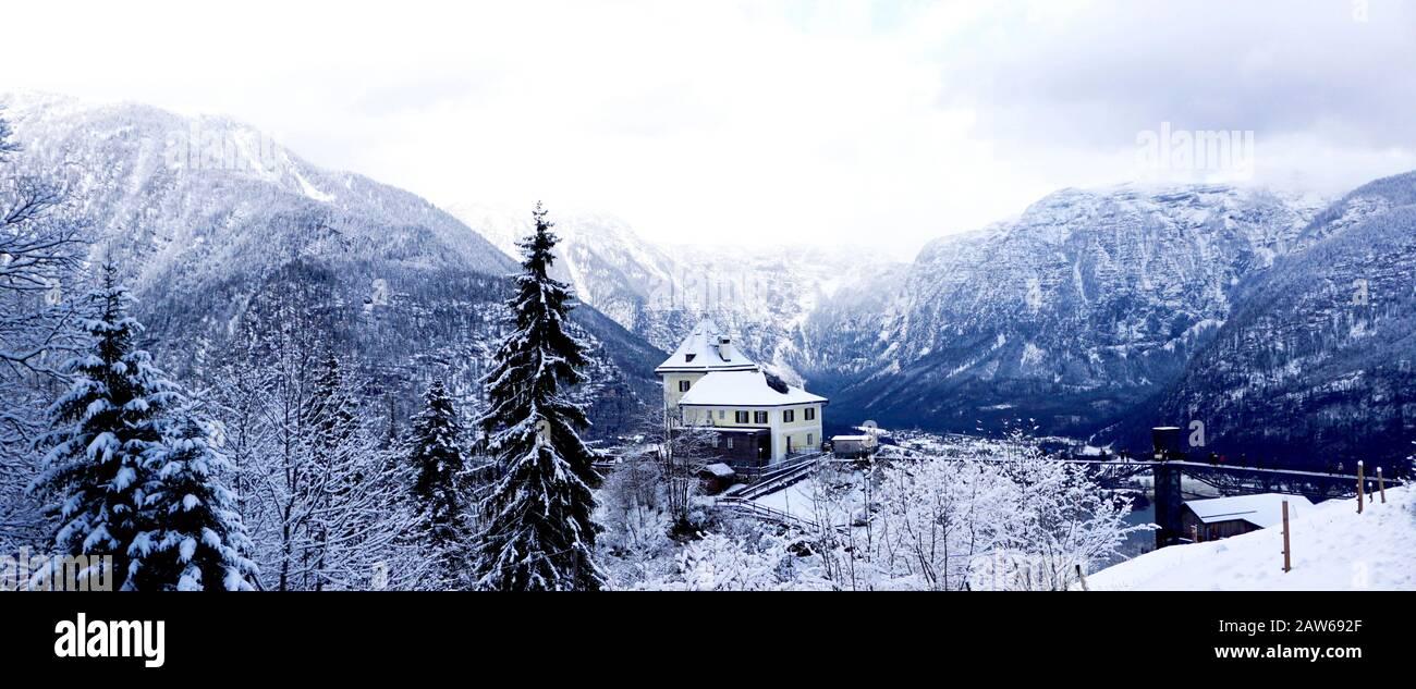 Panorama del paisaje montañoso de nieve de invierno de Hallstatt a través del bosque en el valle del altiplano conduce a la antigua mina de sal de Hallstatt, Austria Foto de stock
