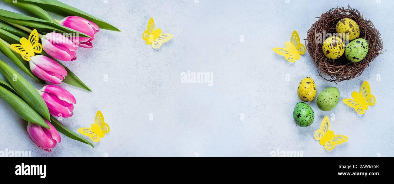Banner De Pascua De Fondo. Huevos de Pascua en Nest y tulipanes rosas en la mesa de piedra azul de fondo. Concepto De Vacaciones De Primavera. Vista superior, espacio de copia, plano Foto de stock