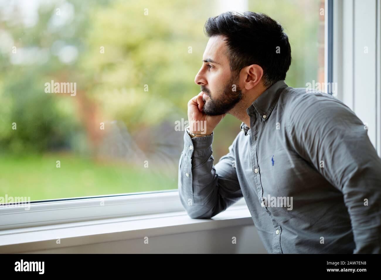 Hombre mirando hacia afuera de la ventana Foto de stock