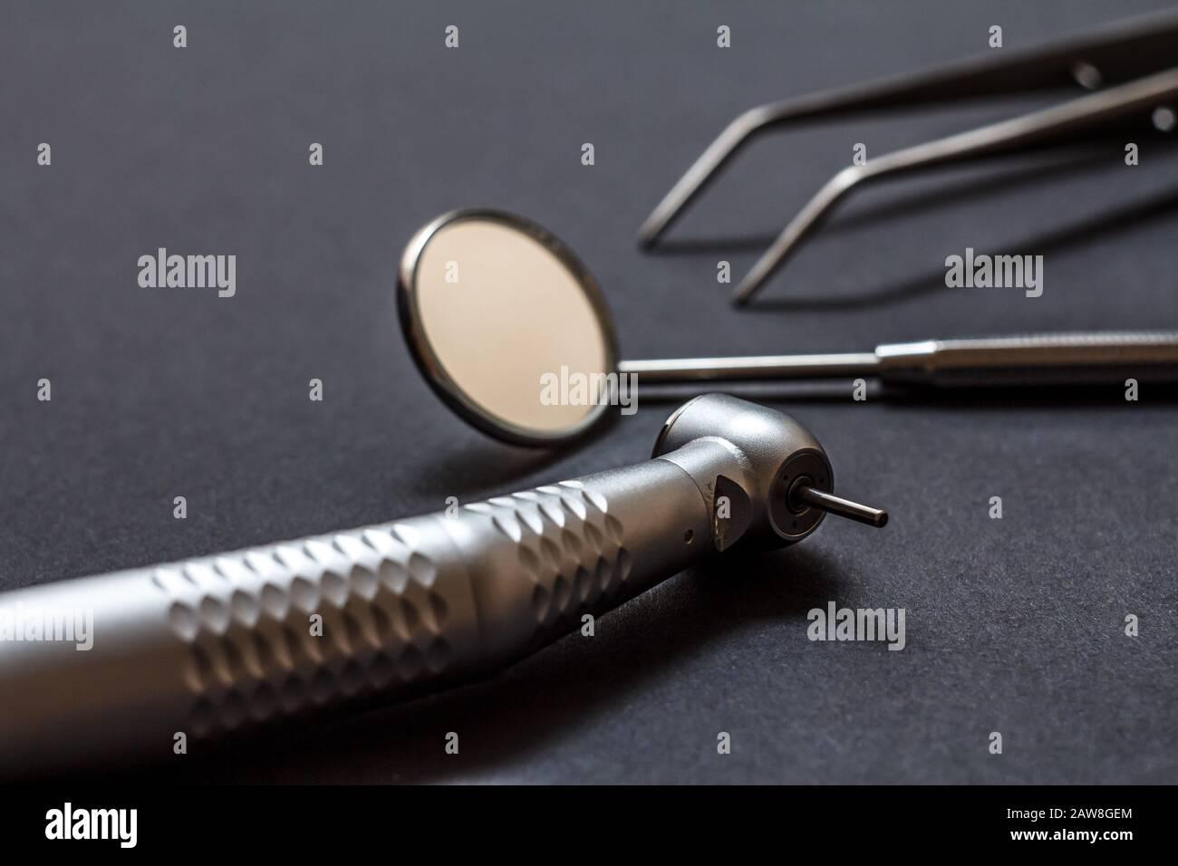 Conjunto de instrumentos dentales metálicos para el tratamiento dental. Pieza dental de alta velocidad, espejo dental y pinzas sobre fondo negro. Herramientas médicas. Shal Foto de stock