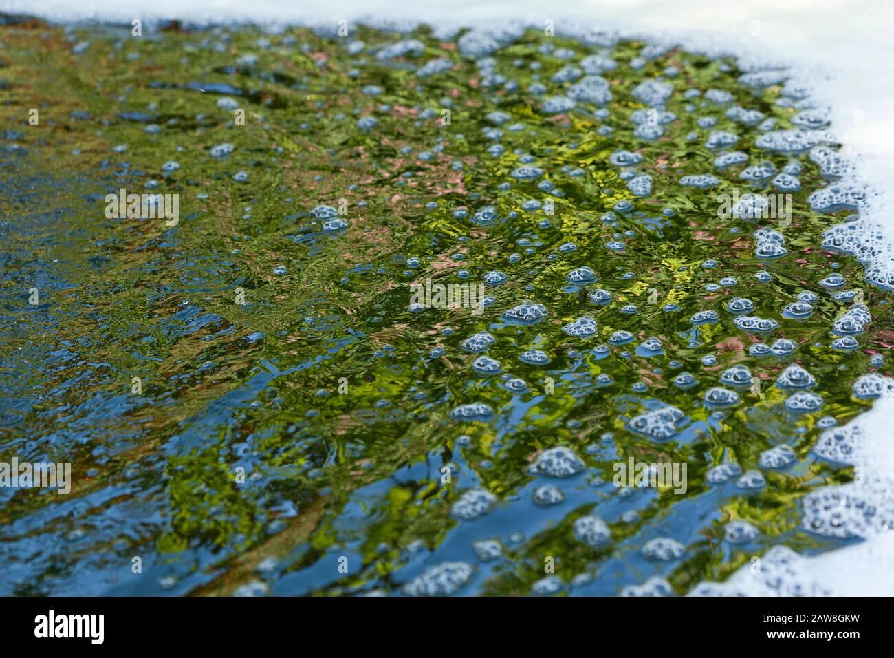 Burbujas, ondulaciones, espuma y reflejos en el agua Foto de stock