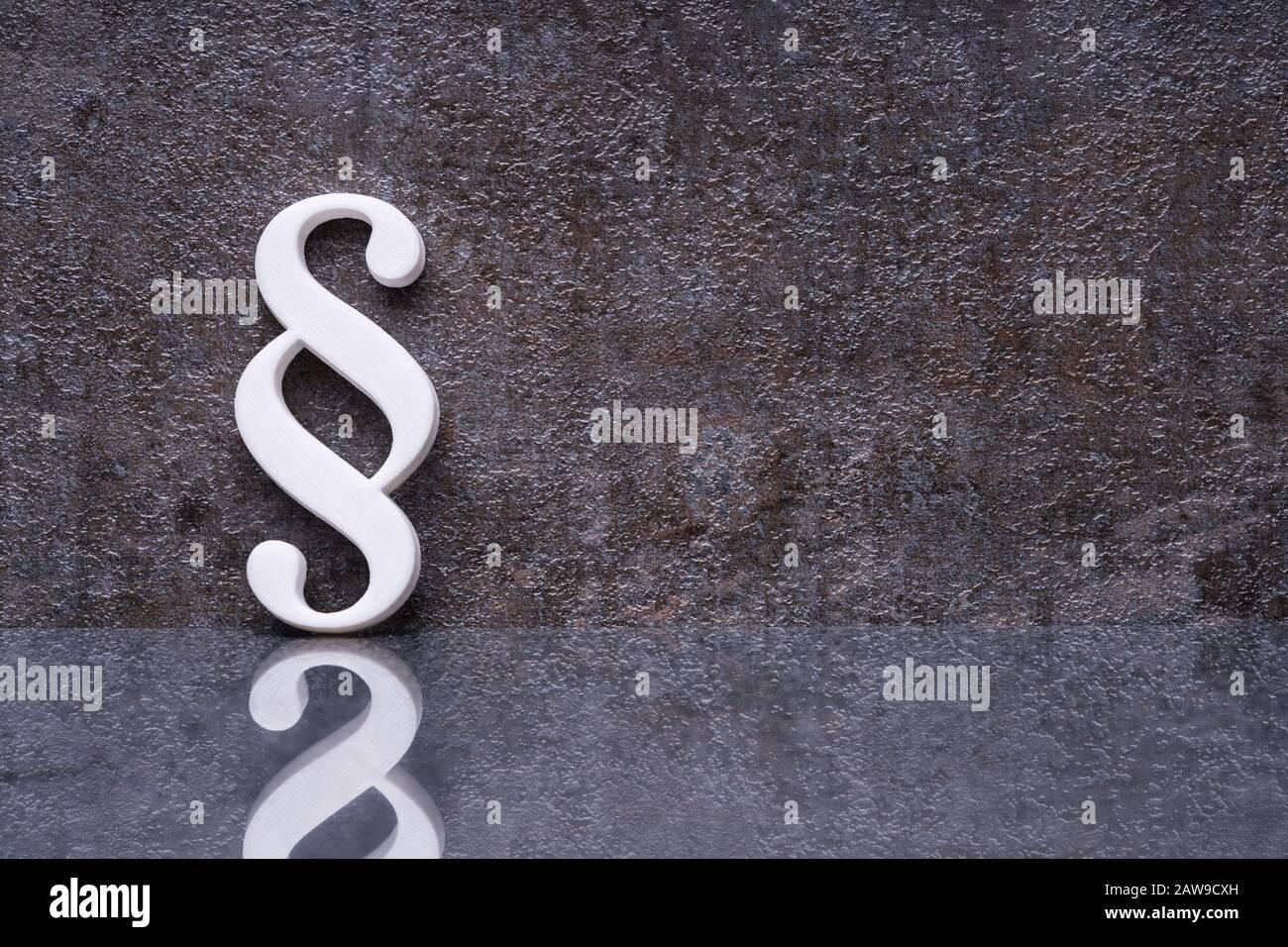 Primer Plano De Un Párrafo Símbolo Inclinada Sobre La Pared Oscura Foto de stock