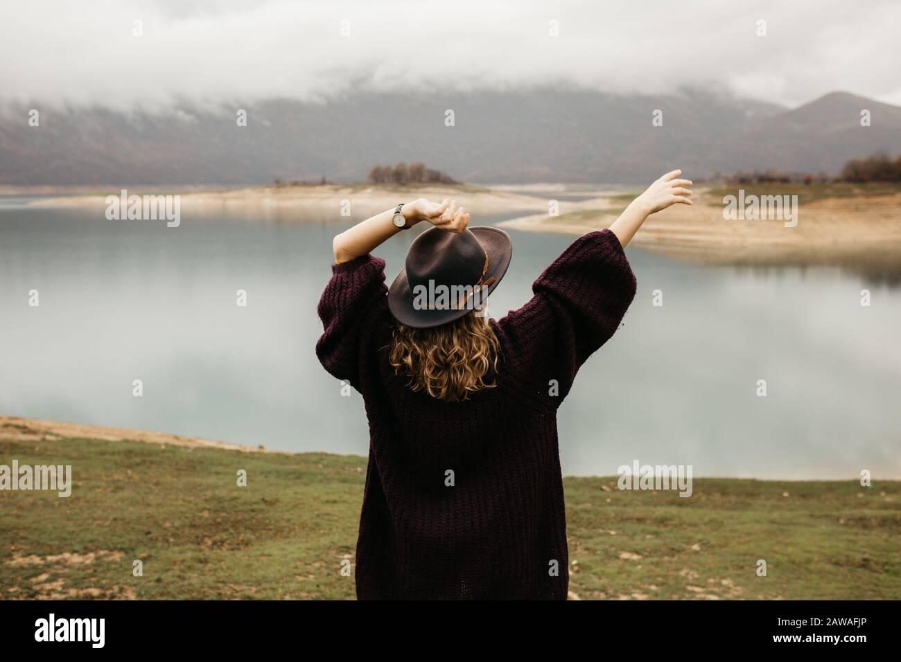Mujer turística explorando el lago. Ella está de pie girada hacia atrás y mirando a distancia, con sus manos en el aire. Foto de stock