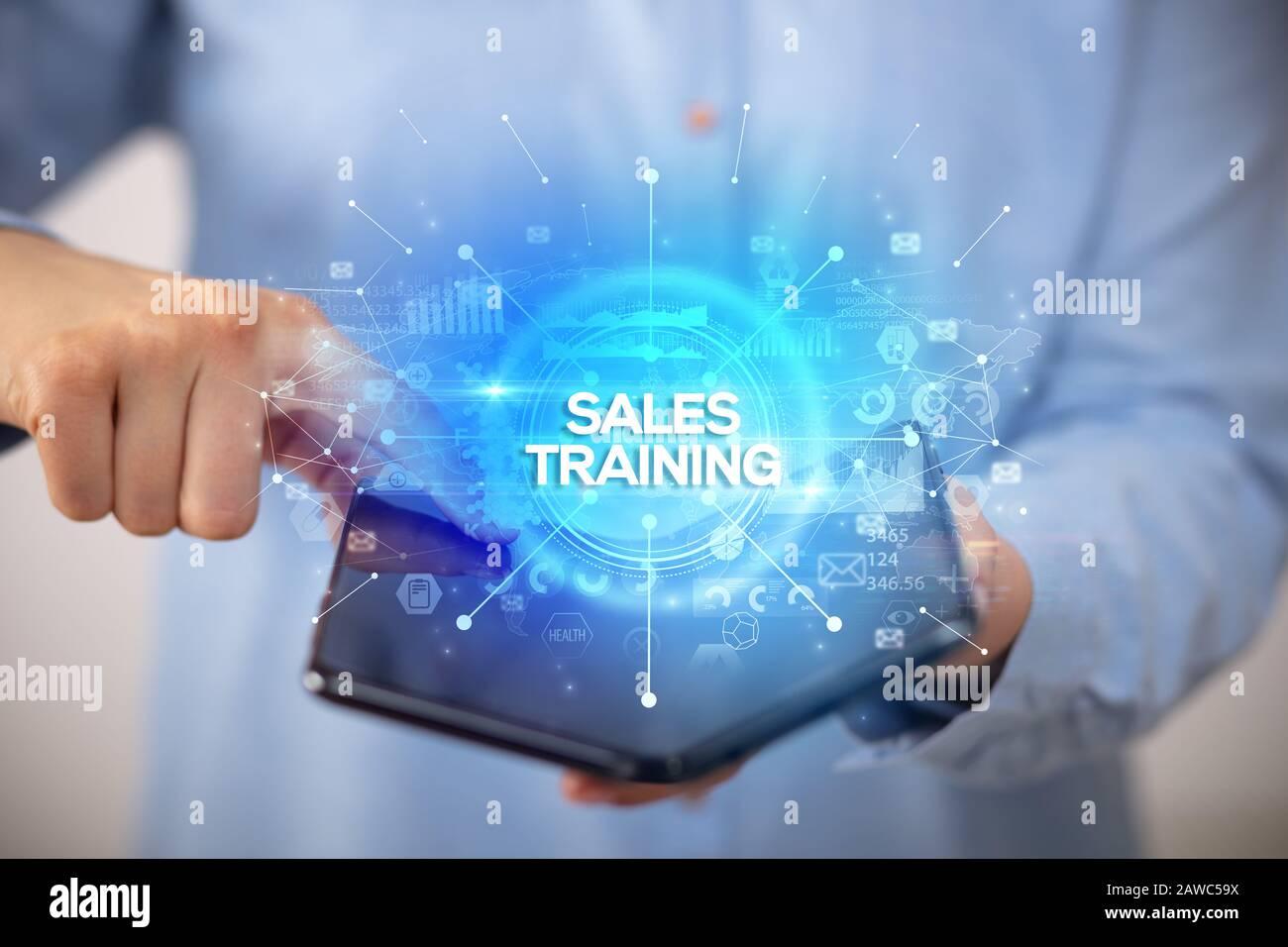 Empresario sosteniendo un plegable con inscripción Formación en ventas de smartphones, el nuevo concepto de negocio Foto de stock