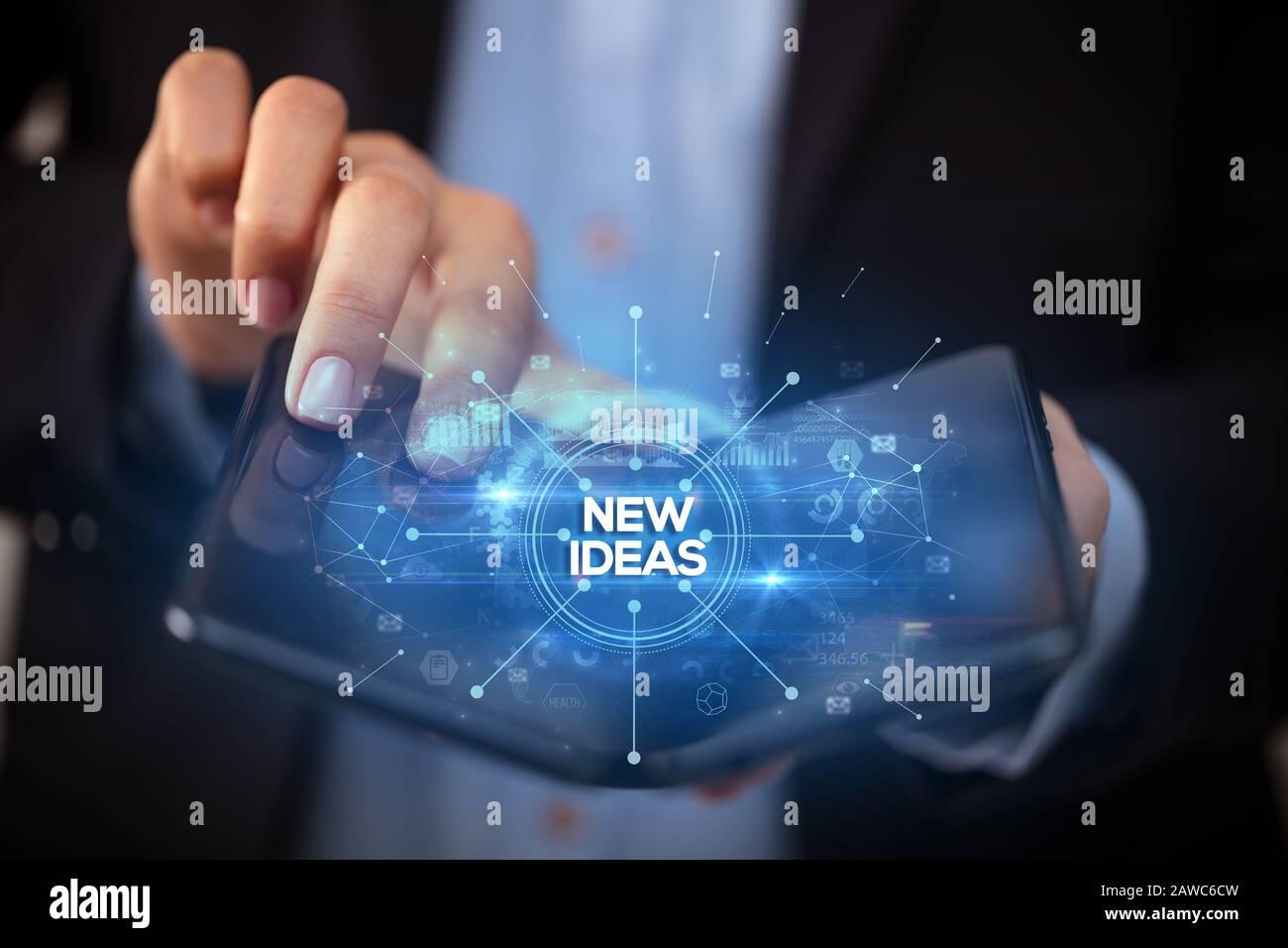 Empresario sosteniendo un smartphone plegable con nuevas ideas, nuevos negocios concepto de inscripción Foto de stock