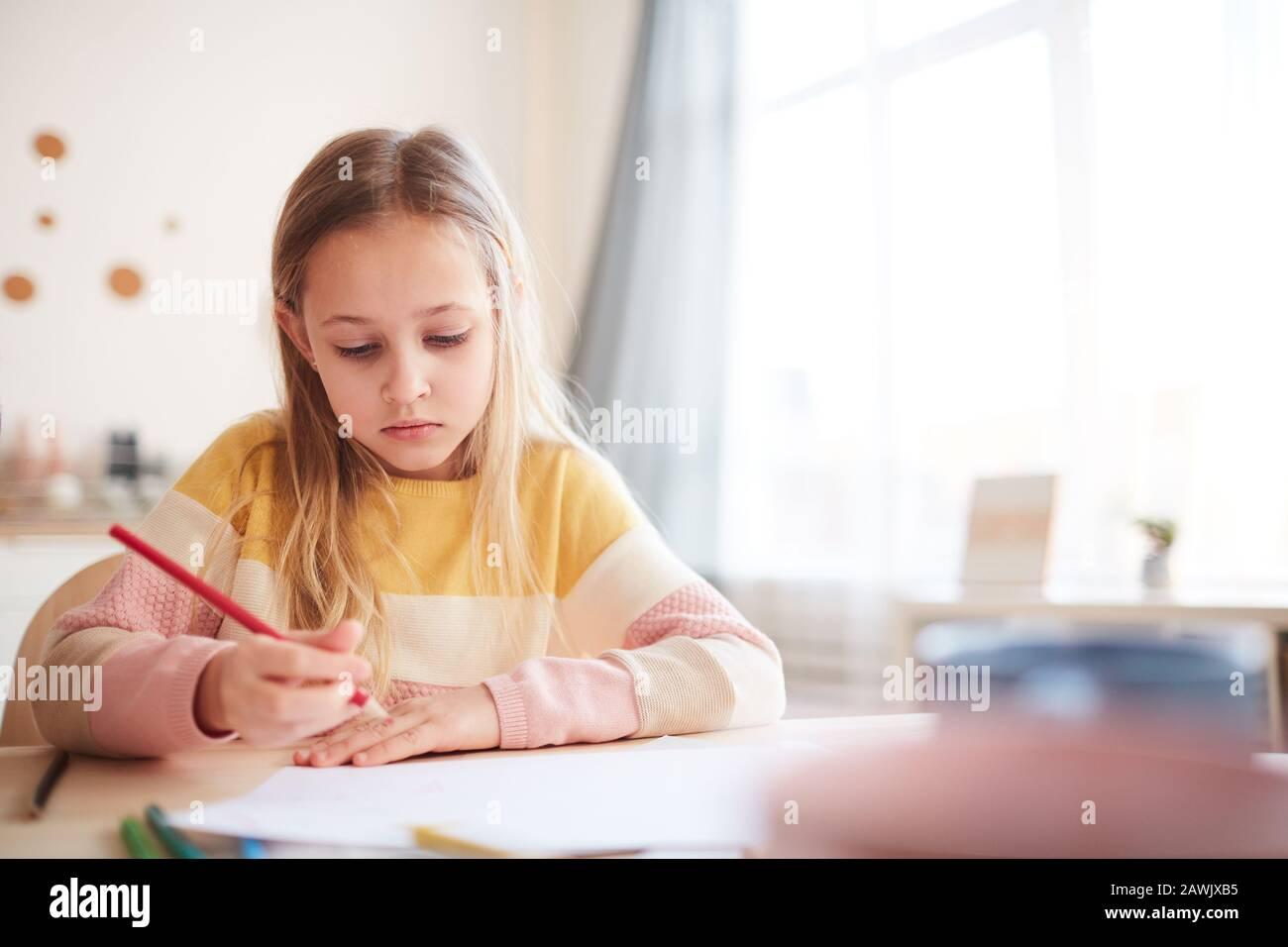 Cálido retrato tonificado de una linda niña dibujando fotos o haciendo tareas mientras está sentado en la mesa en el interior de casa, espacio para copiar Foto de stock