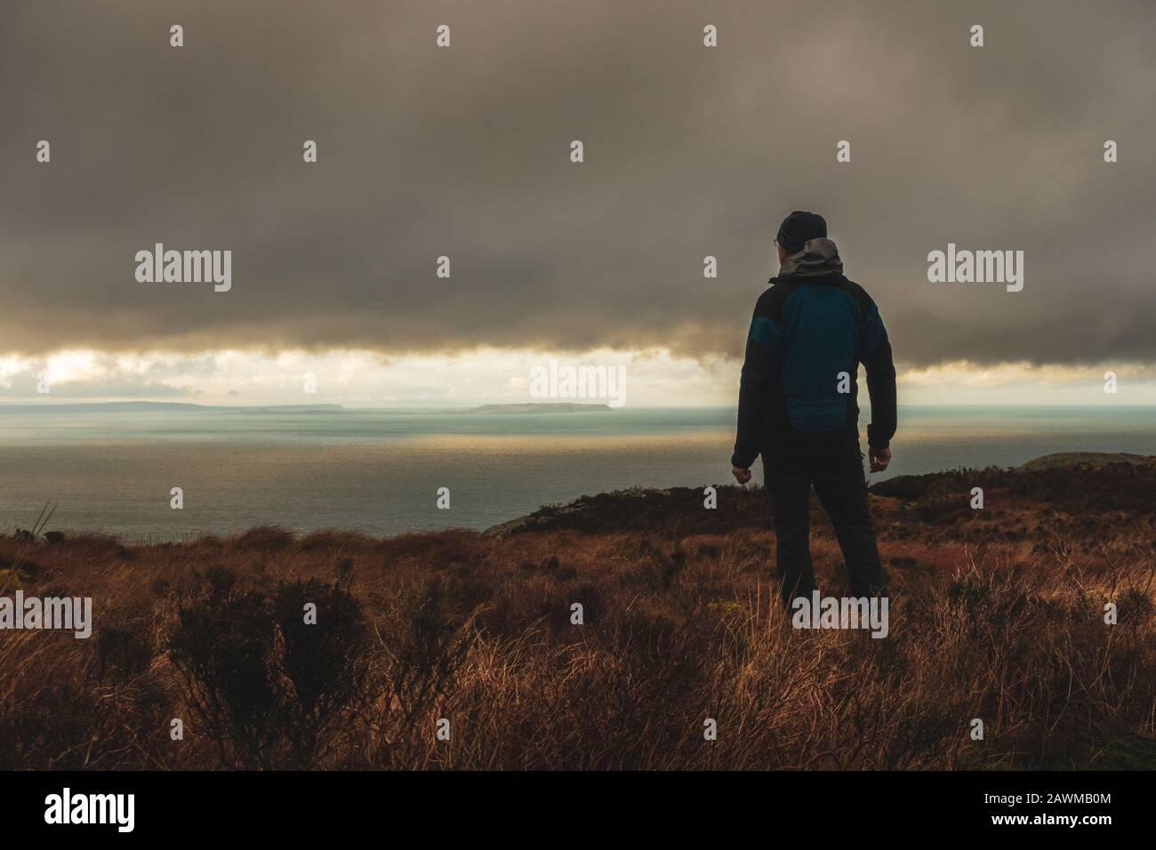 Persona admirando las vistas desde el Mull of Kintyre a Irlanda del Norte y la isla Rathlin en condiciones meteorológicas dramáticas en invierno, Escocia, Reino Unido Foto de stock