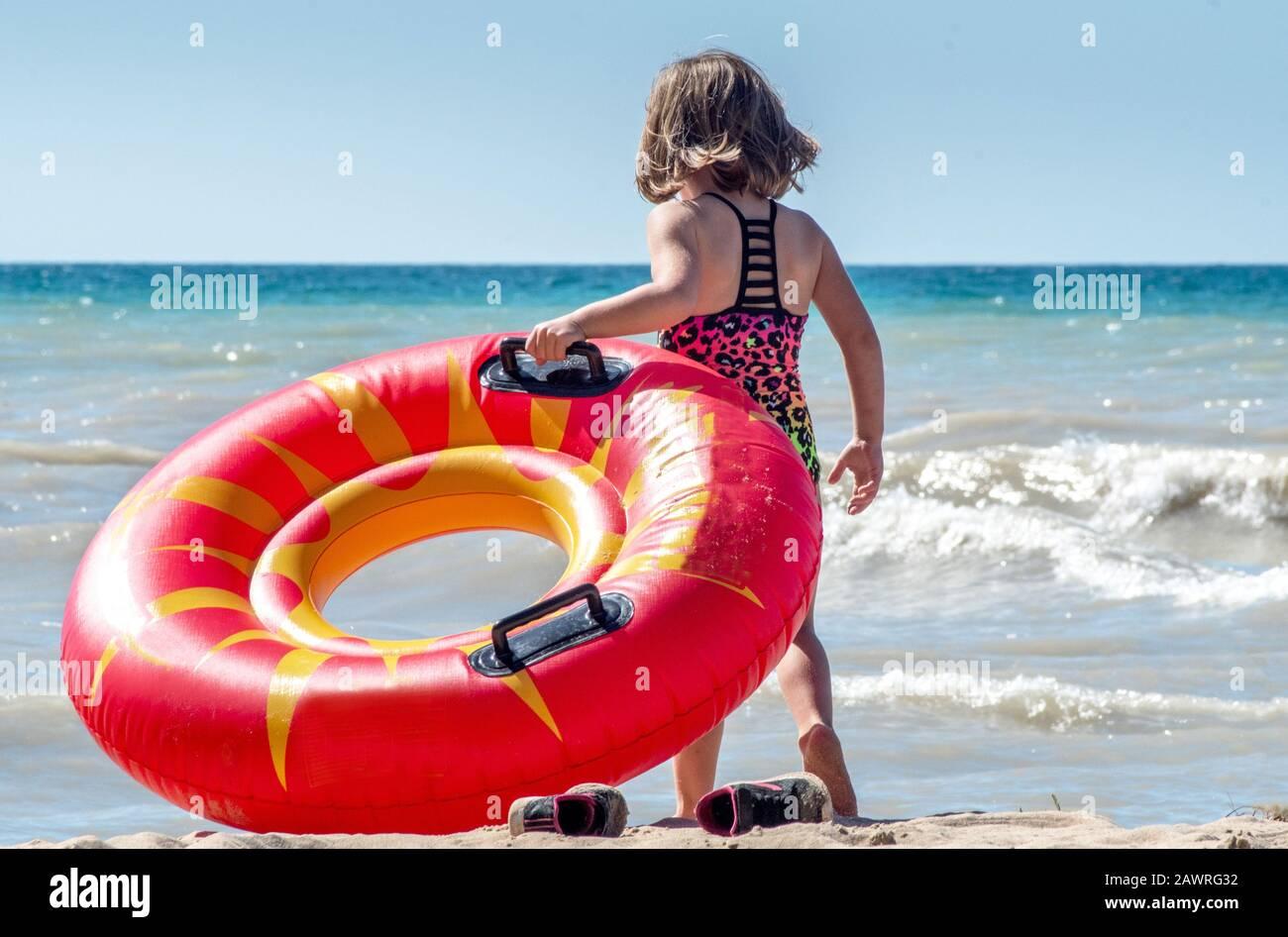 Una niña arranca sus zapatillas de deporte y se prepara para llevar su juguete flotante a las aguas activas del lago Michigan en los Estados Unidos Foto de stock