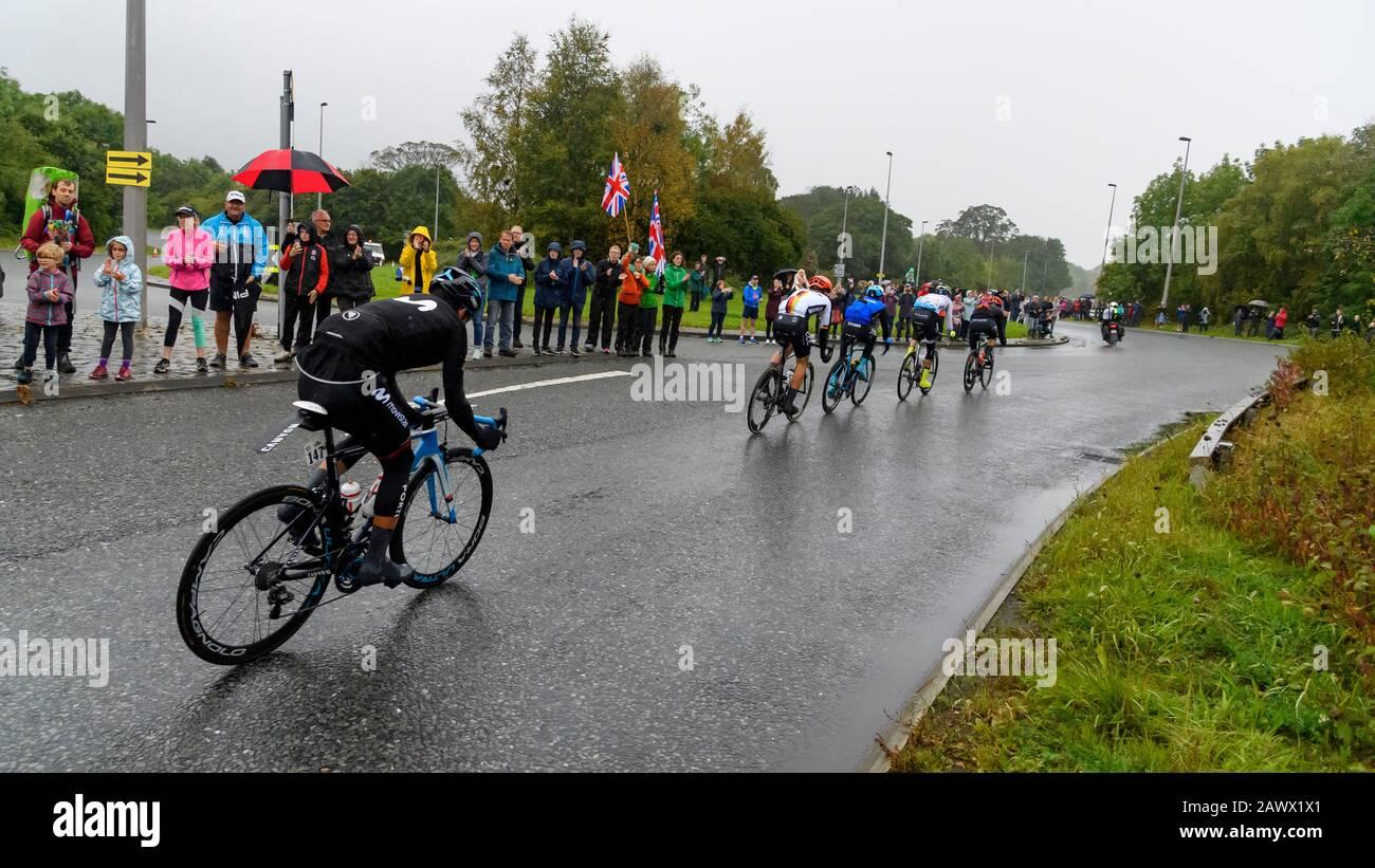 Carreras de bicicleta de carretera para hombres (ciclistas en bicicletas en pelotón) montar y competir en carrera vigilada por los seguidores en la lluvia - Campeonato Mundial UCI, Yorkshire, Reino Unido Foto de stock
