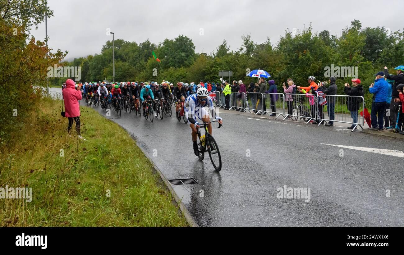 Hombres carreras de bicicletas de carretera (ciclistas pelotón en bicicletas) montar y competir en la carrera vigilada por los aficionados mojados en la lluvia - Campeonato del Mundo UCI, Yorkshire Reino Unido Foto de stock