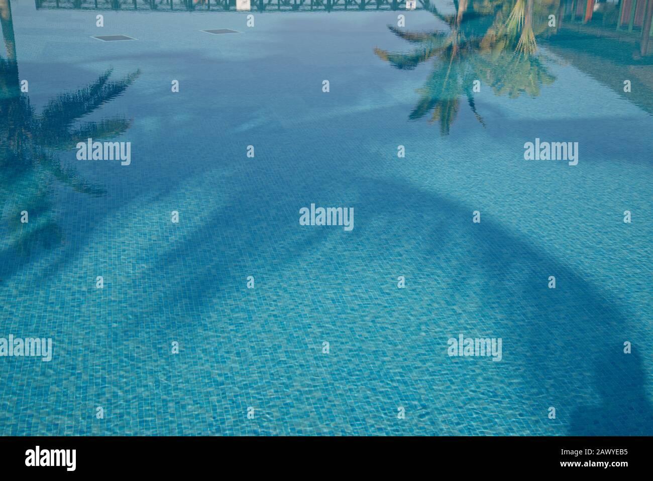 Reflexiones en piscinas azules con palmeras tropicales. Piscina de azulejos de mosaico azul. Foto de stock