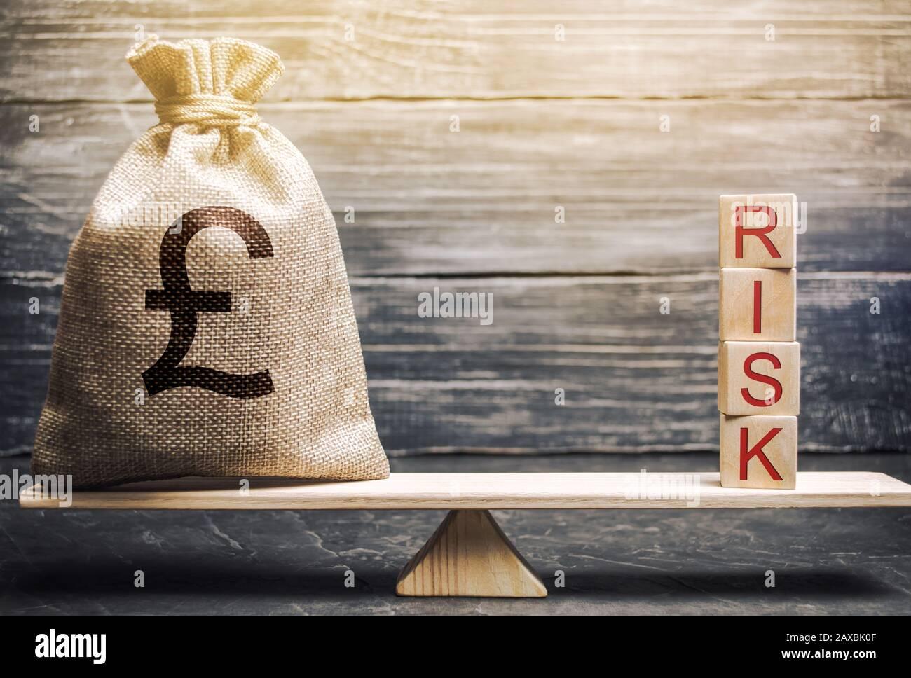 Bolsa de dinero y bloques de madera con la palabra Riesgo en las escalas. Gestión y evaluación de riesgos empresariales. Riesgos estratégicos, financieros y operativos. In Foto de stock