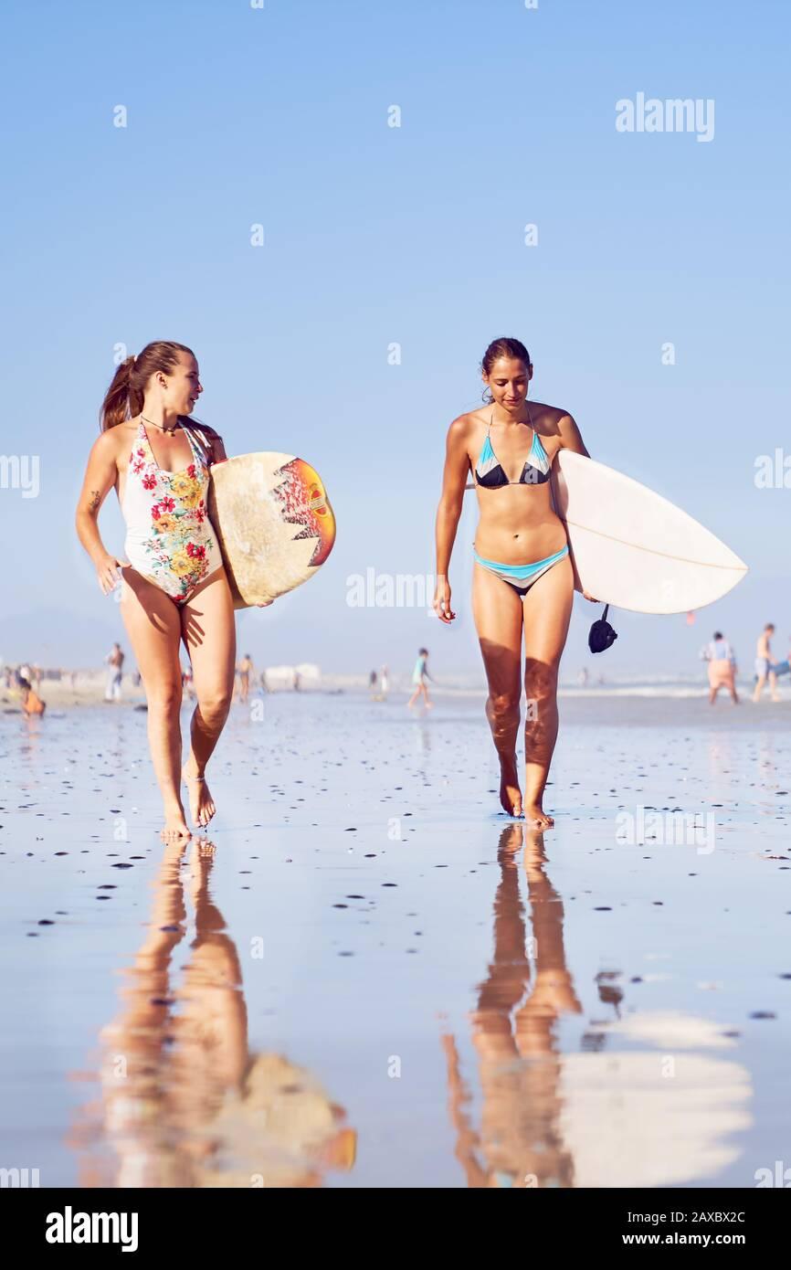 Jóvenes surfistas con tablas de surf en la playa soleada Foto de stock