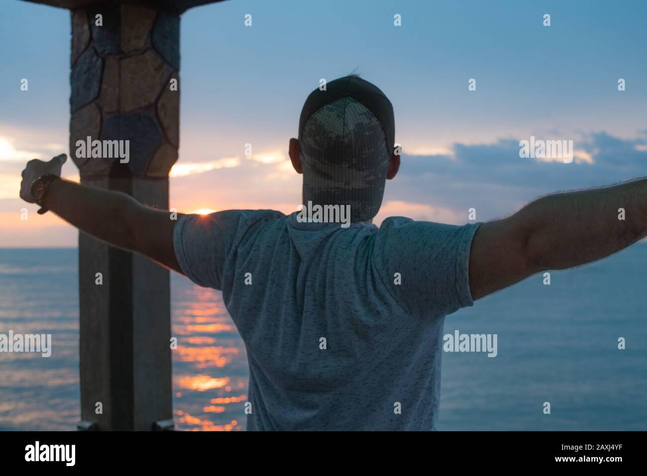 Hombre que abre sus brazos a la vista del mar y encuentra paz. Concepto De Libertad. Foto de stock