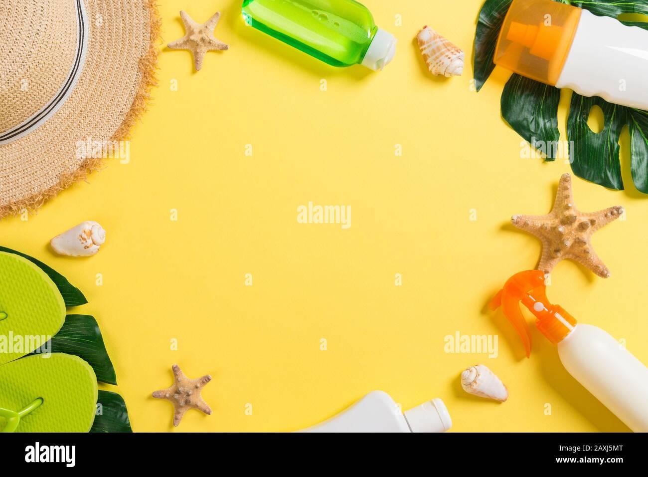 Accesorios de playa con sombrero de paja, bronceador y seastar sobre fondo amarillo vista superior con espacio de copia. Foto de stock