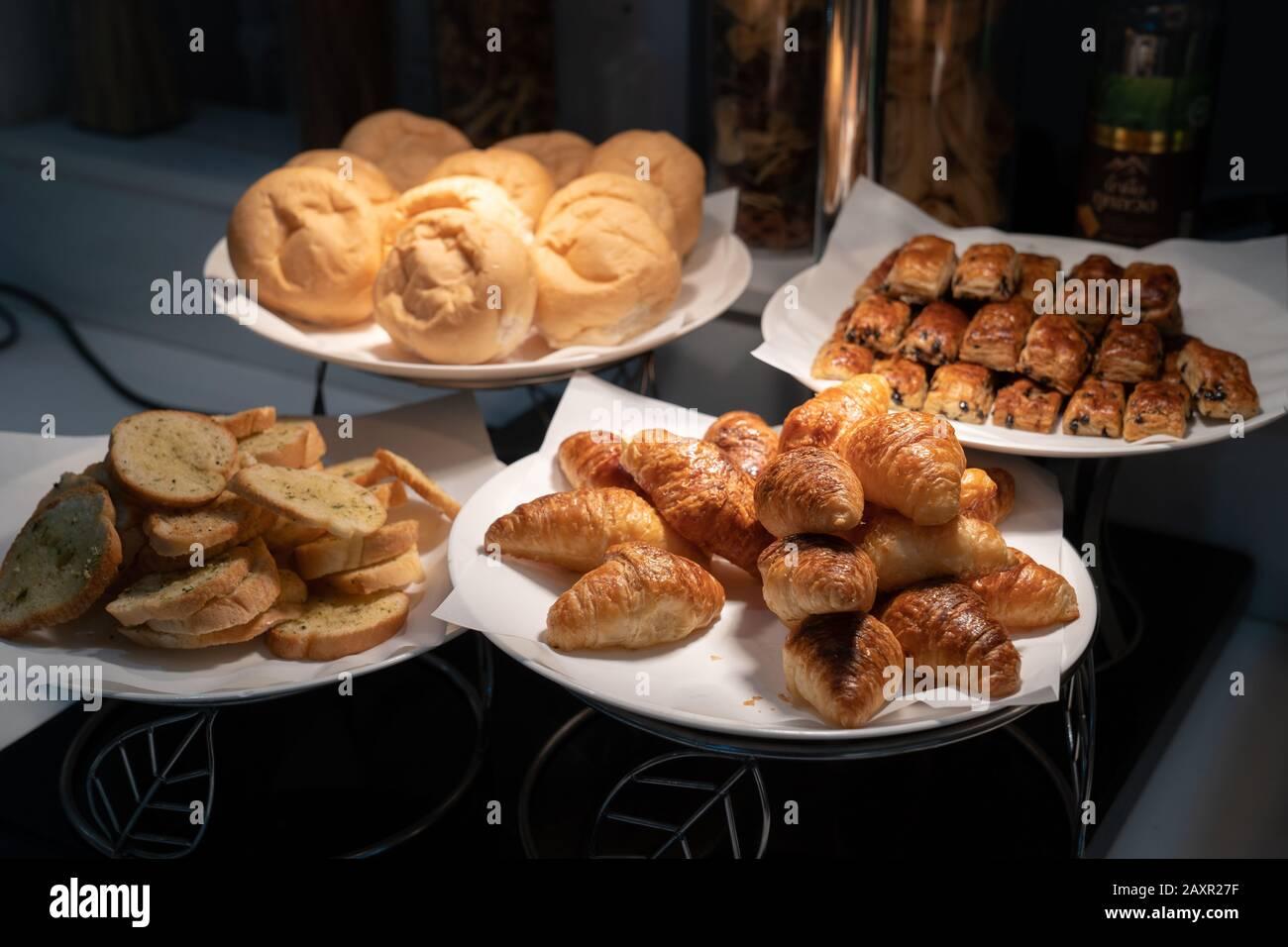 El croissant y el pan en papel y el plato blanco en la oscuridad están decorados con luz de tungsteno de la lámpara. Foto de stock