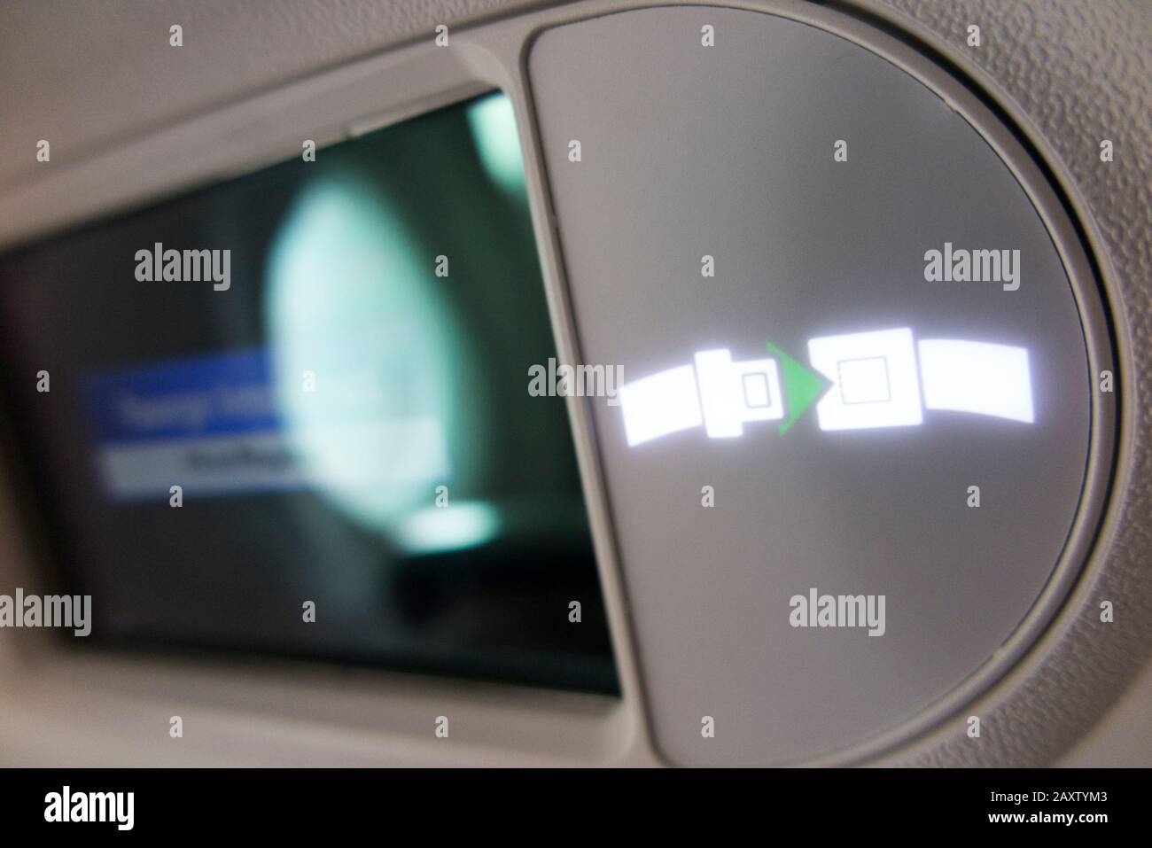"""La señal de luz superior del avión """"Cinturón De Seguridad/cinturón de seguridad"""" se enciende e ilumina durante el vuelo en un avión Bombardier. (112) Foto de stock"""