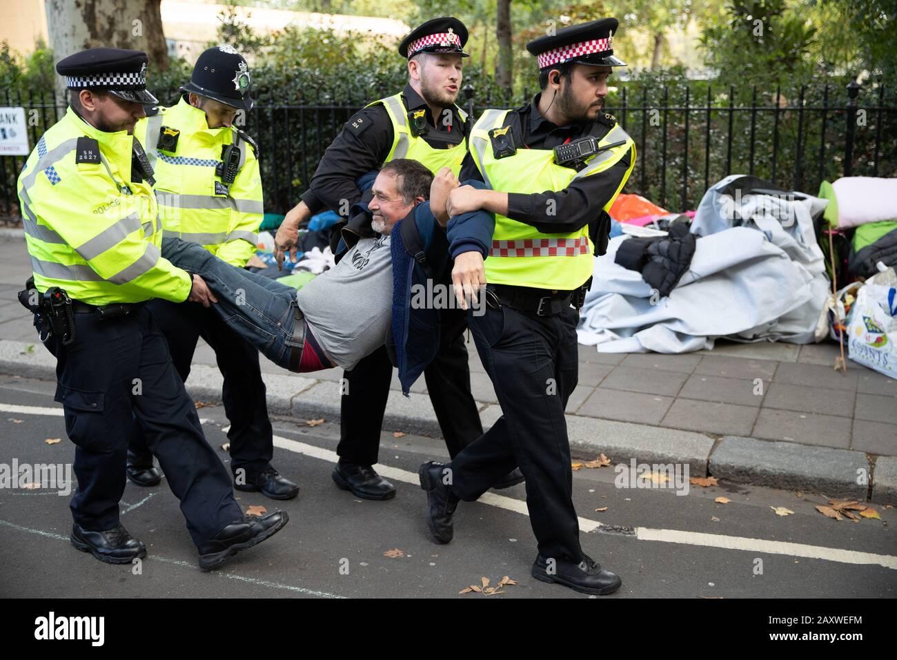 Londres, Reino Unido. 08 OCT 2019. Una persona conducida por un miembro de la Policía Metropolitana durante La Extinción Rebelión Internacional Rebelión Foto de stock