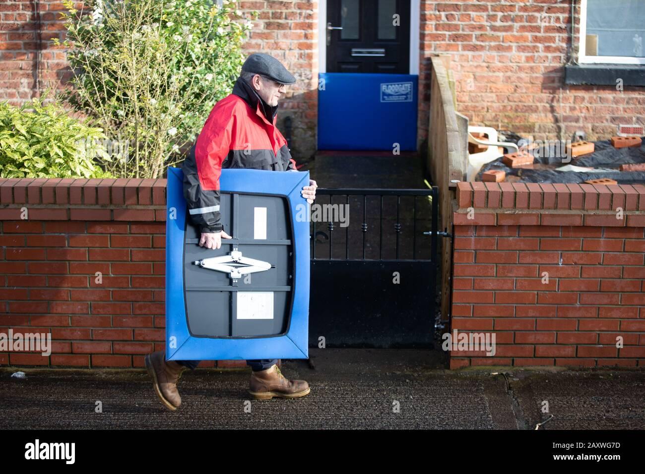 Bury, Reino Unido. 09 DE FEBRERO DE 2020. Una persona toma un dispositivo de prevención de inundaciones para detener la entrada de agua en su casa durante la tormenta Ciara. La tormenta Ciara causó f Foto de stock