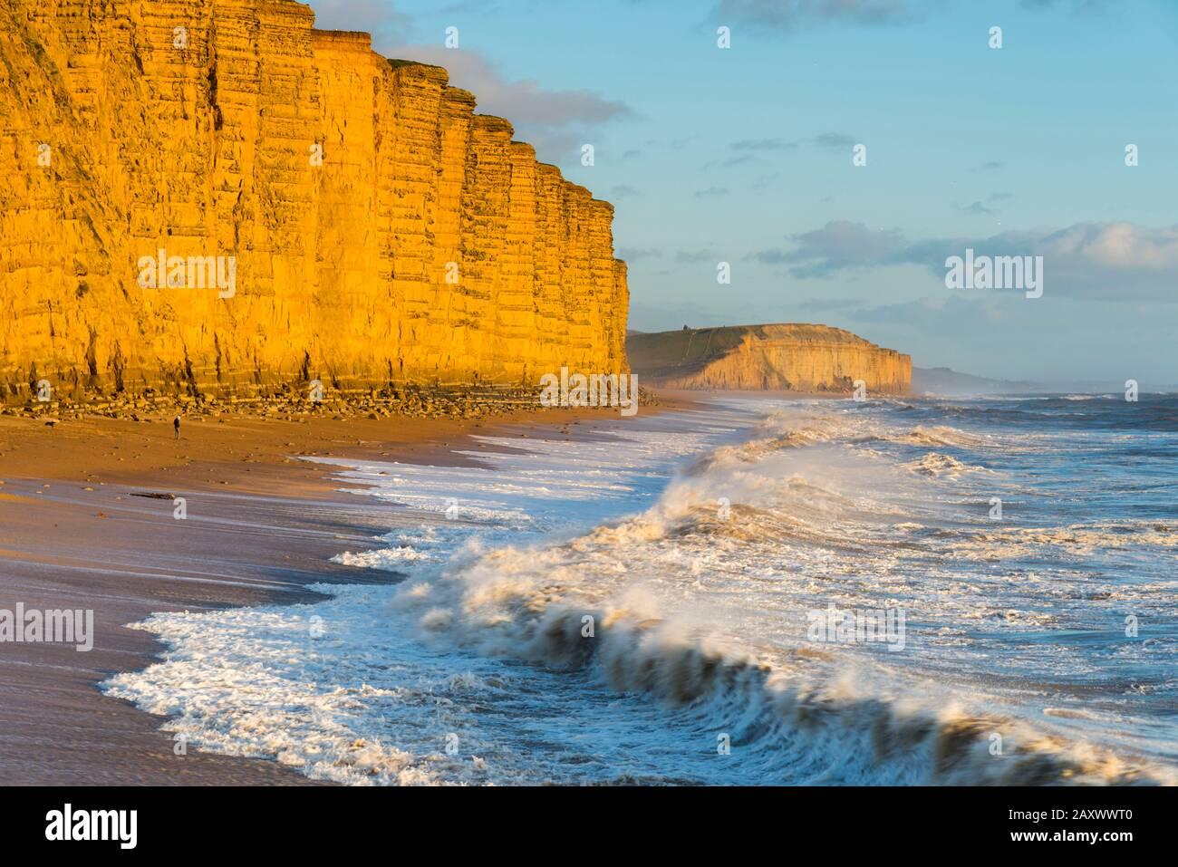 West Bay, Dorset, Reino Unido. 13 de febrero de 2020. Clima en el Reino Unido. Los mares accidentados rompen en tierra en East Beach, en West Bay, en Dorset, mientras los acantilados de arenisca brillan en una naranja dorada en una tarde soleada poco antes de la puesta de sol. Crédito De La Imagen: Graham Hunt/Alamy Live News Foto de stock