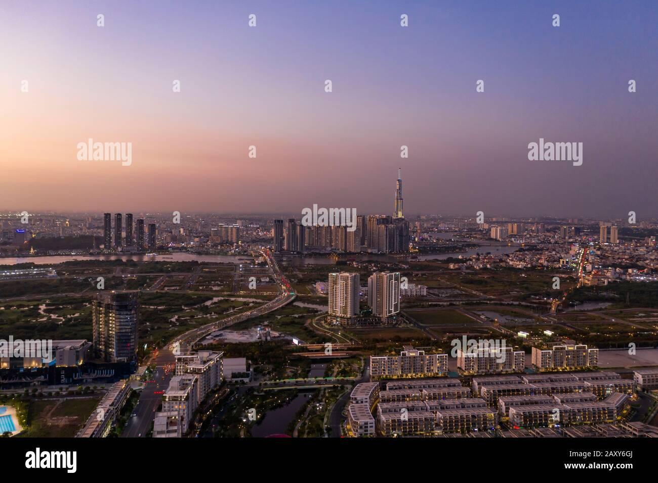 Vista aérea a los nuevos desarrollos inmobiliarios de lujo a lo largo del río Saigón desde el distrito de Jue Thiem, en Ciudad Ho Chi Minh, Vietnam al atardecer Foto de stock