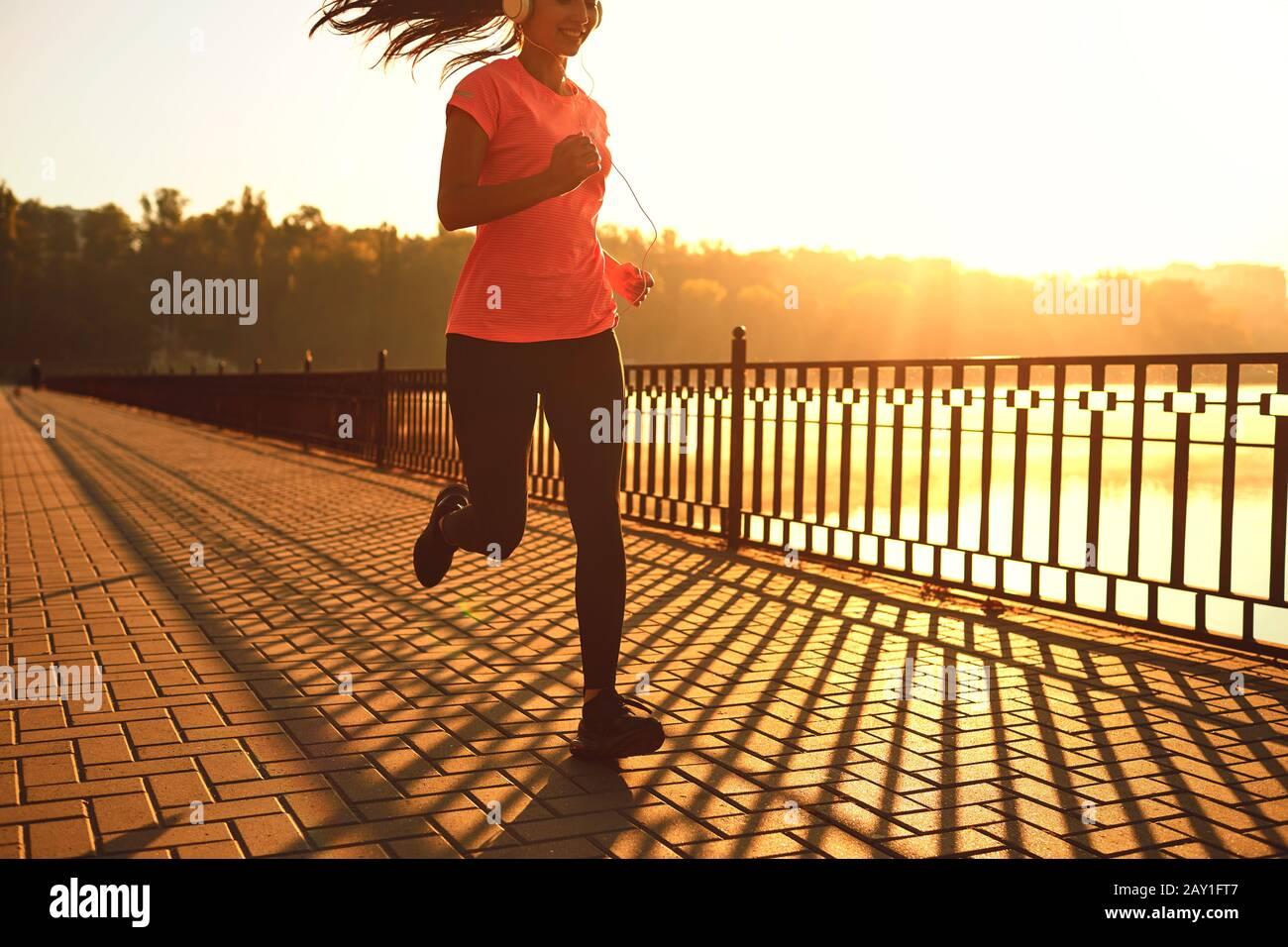 Runner corre en la carretera en el sol al atardecer en un parque de otoño. Foto de stock