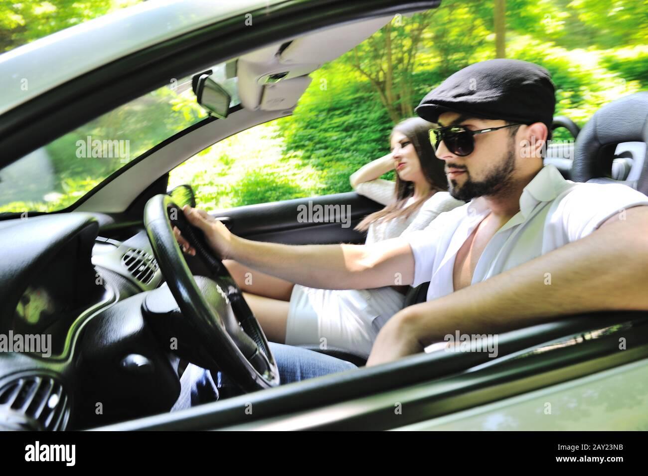 Pareja hermosa disfrutando de la naturaleza en un coche deportivo Foto de stock