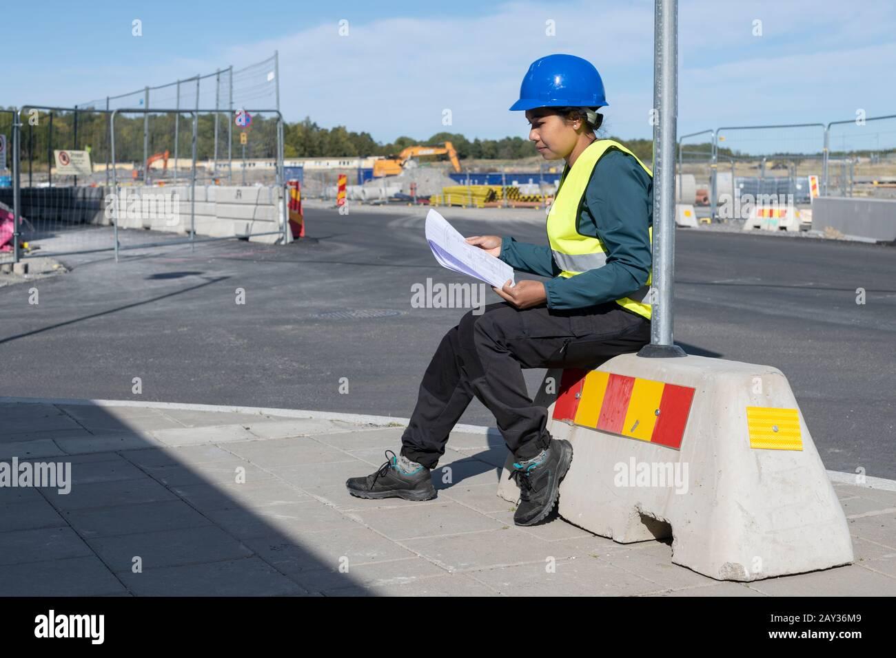 Mujer sosteniendo un plano en el sitio de la construcción Foto de stock
