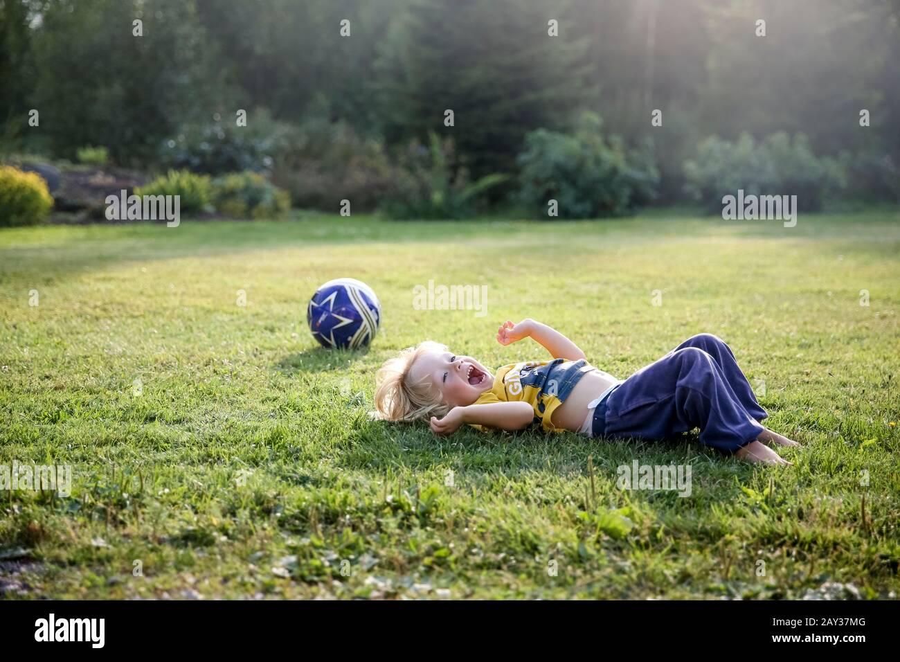 Niño feliz tumbado en el césped Foto de stock
