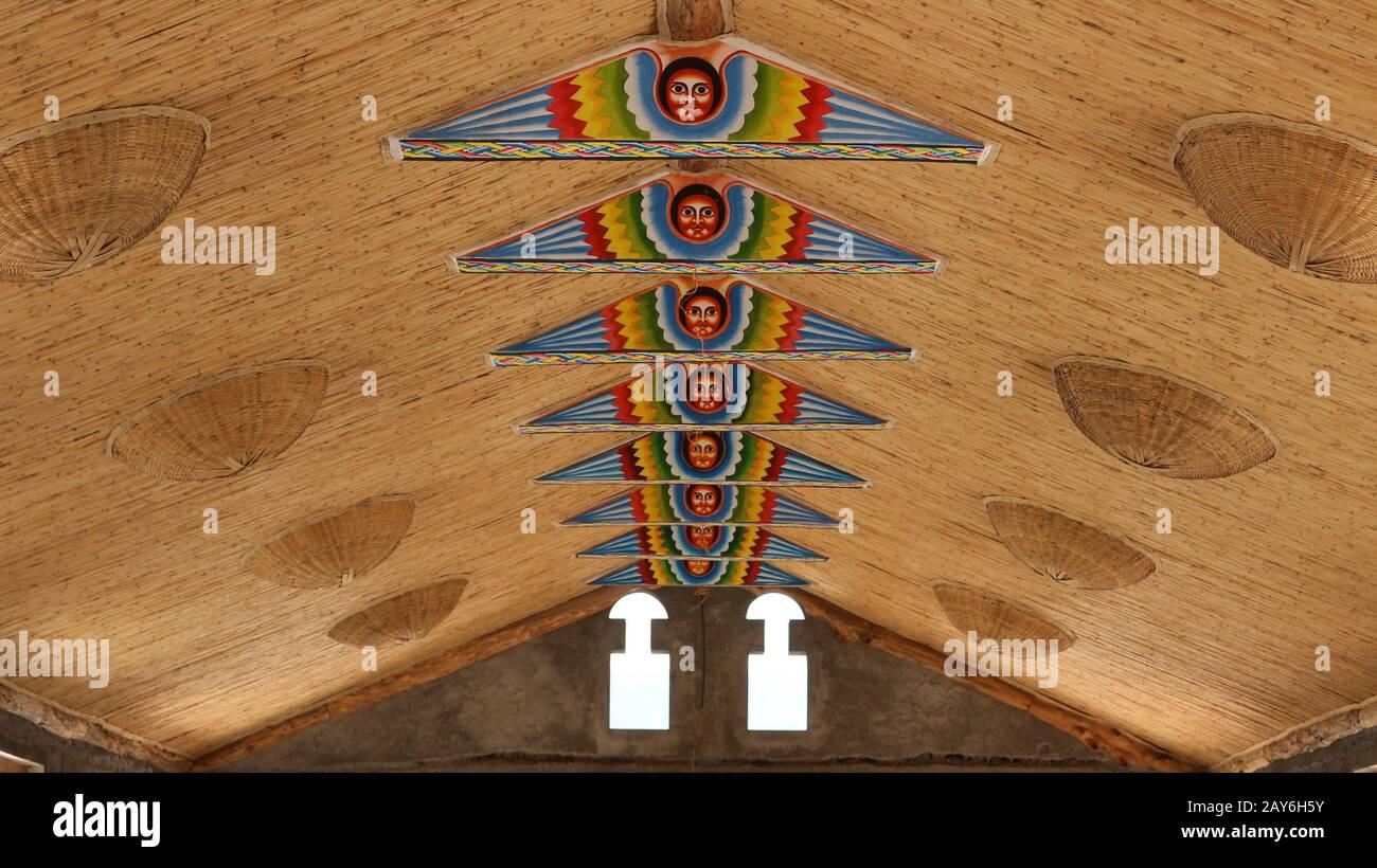 La pintura tradicional de la cara etíope decora las vigas de madera de un techo tradicional africano de paja de un salón en Lalibela, Etiopía Foto de stock