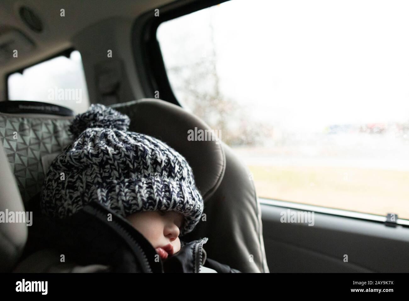 El niño que lleva sombrero de invierno duerme mientras está en el asiento del coche dentro del monovolumen Foto de stock