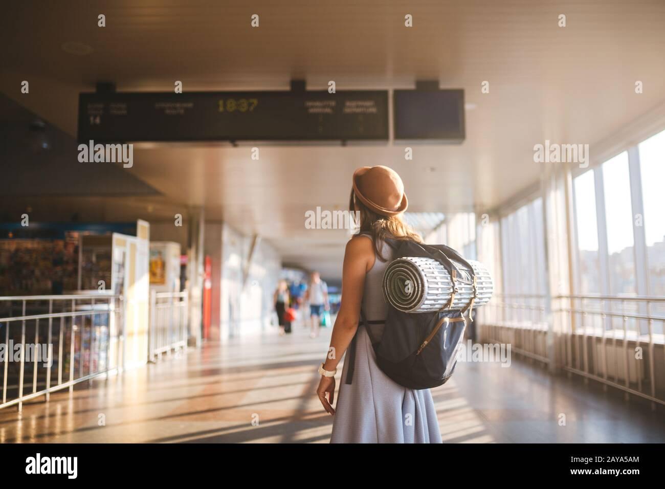 Viaje temático transporte público. Mujer joven de pie con espalda vestida y sombrero detrás de mochila y equipo de camping para dormir Foto de stock
