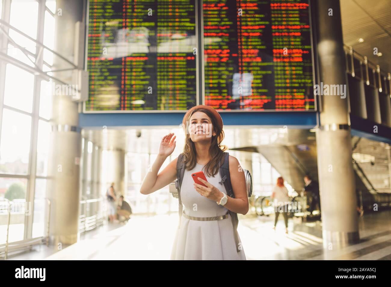 Viaje temático y transporte. Hermosa mujer caucásica joven en vestido y mochila de pie dentro de la estación de tren o terminal de baño Foto de stock
