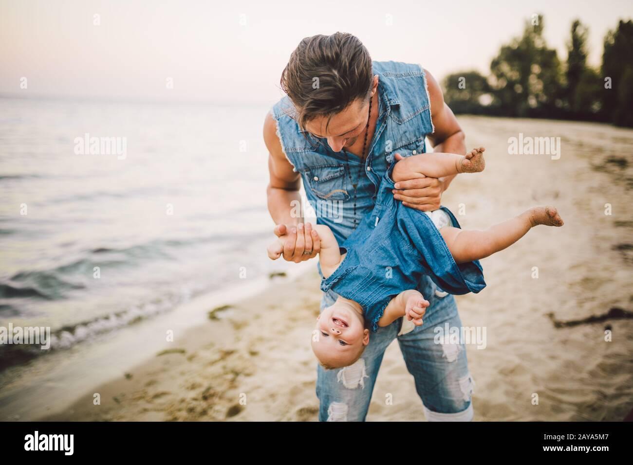Tema la paternidad y el descanso con un niño en el mar. Joven guapo padre caucásico juega juega disfruta tirar en brazos a su hijo Foto de stock