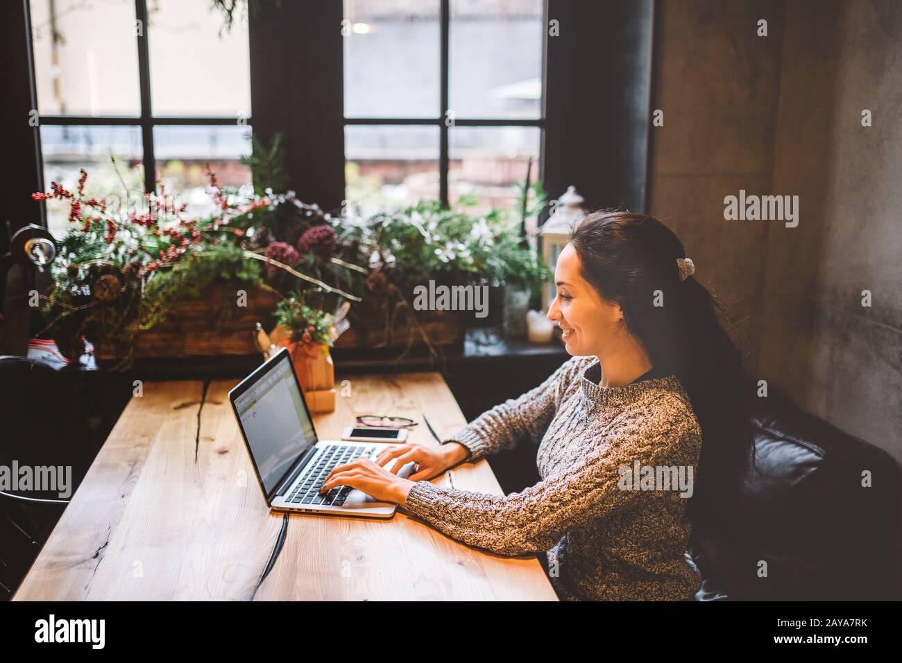 hermosa mujer joven morena usando un ordenador portátil en una cafetería en una mesa de madera cerca de la ventana escribiendo texto en un teclado. En invierno, Foto de stock