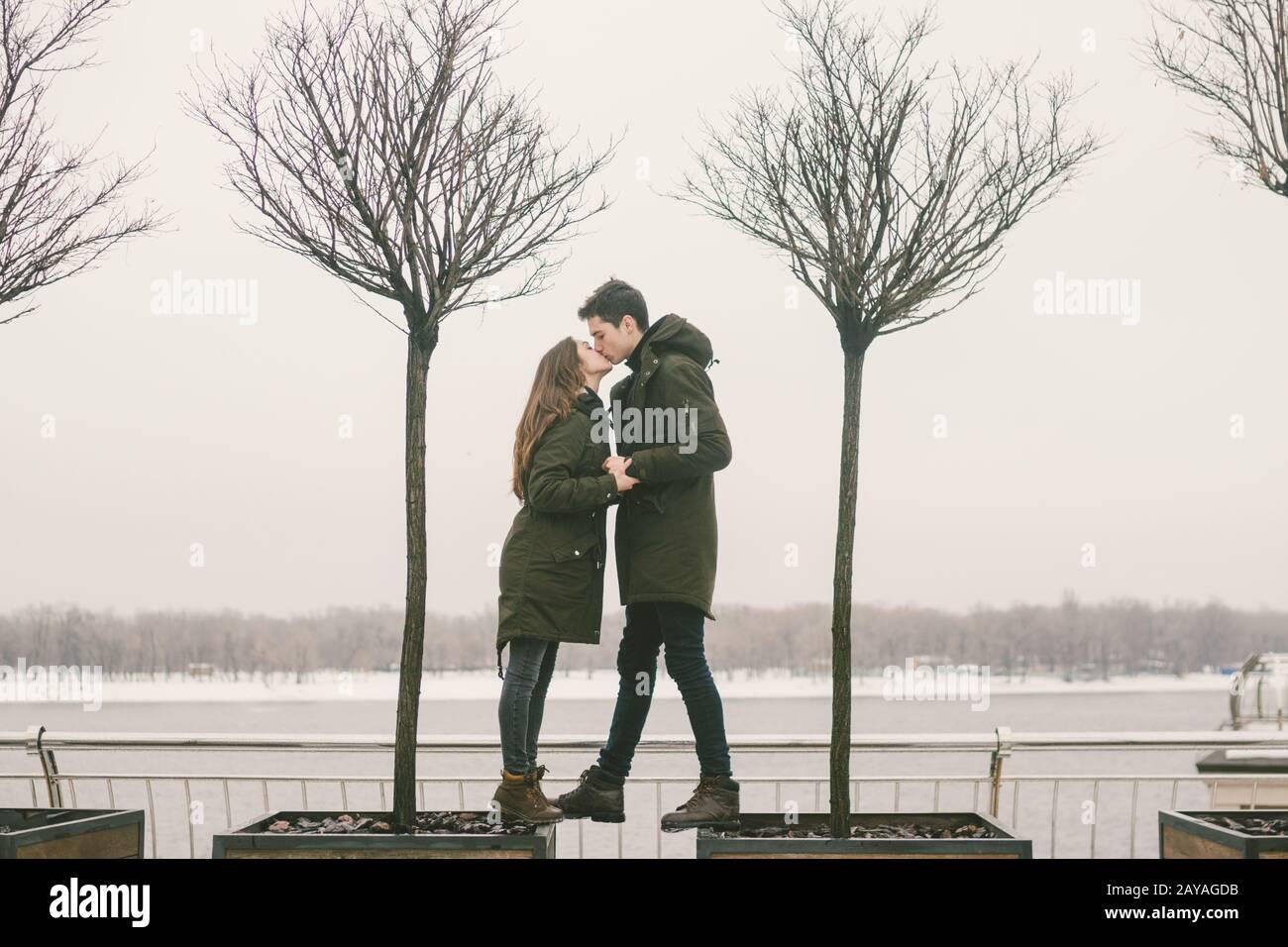 Una pareja heterosexual de jóvenes enamorados alumnas a un hombre y a una mujer caucásica. En invierno, en la plaza de la ciudad cubierta de hielo, Foto de stock