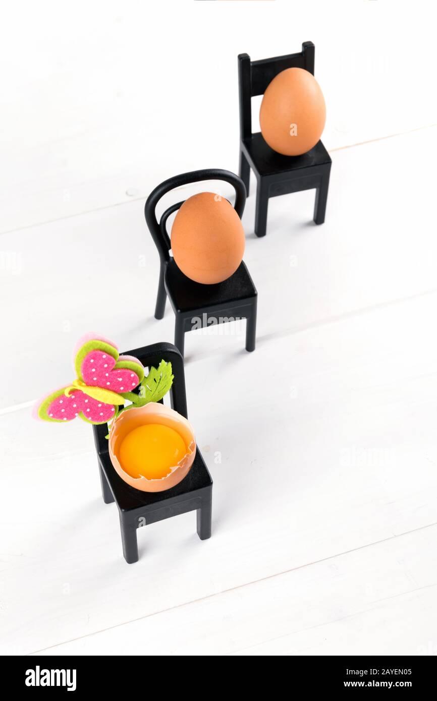 Tres huevos naturales están sentados en silla negra con decoración de flores de pascua. Minimale idea de concepto de pascua. semana santa o semana santa, enfoque selectivo Foto de stock