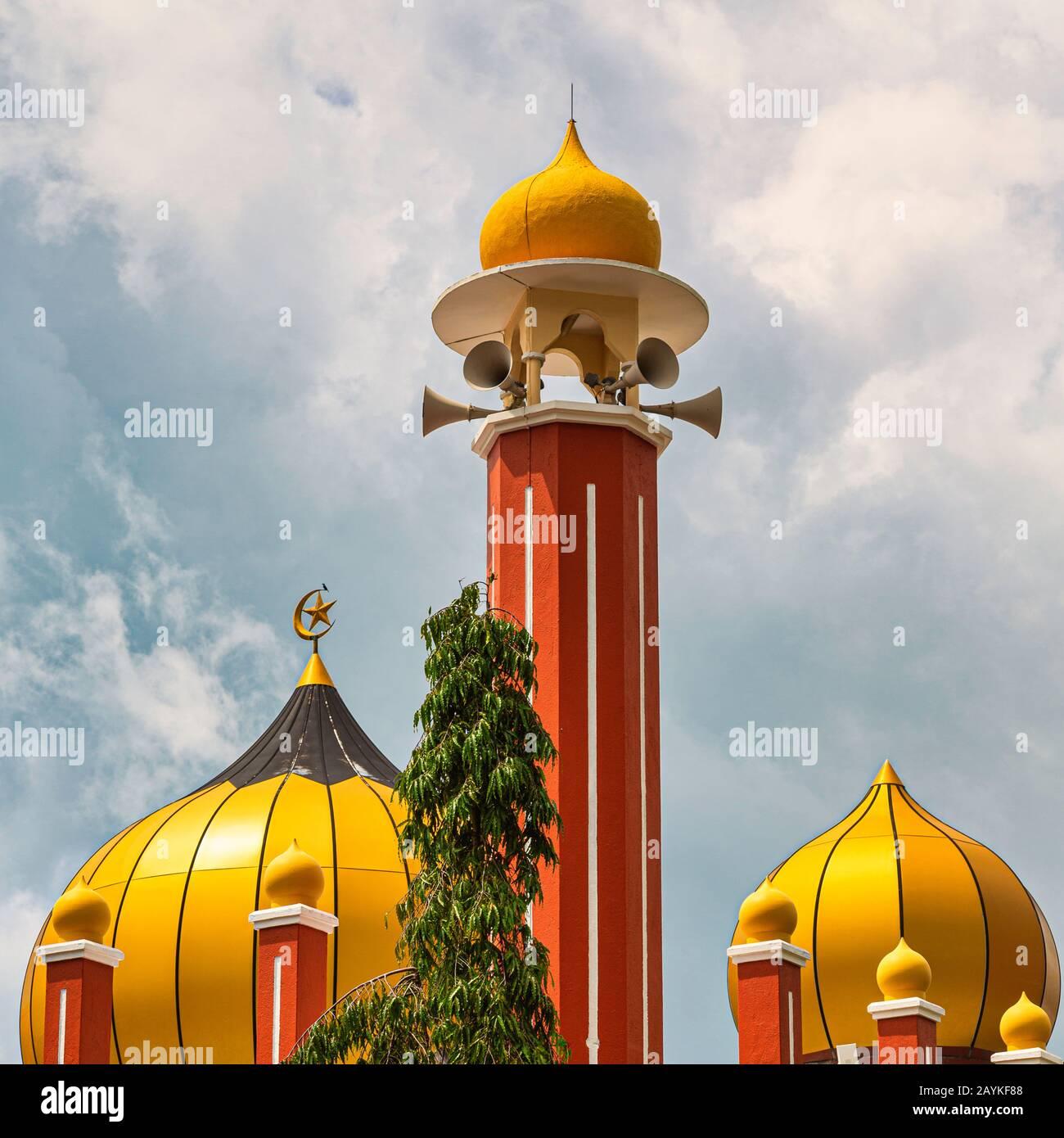 Tormenta nube fondo al minarete de la mezquita dorada Foto de stock