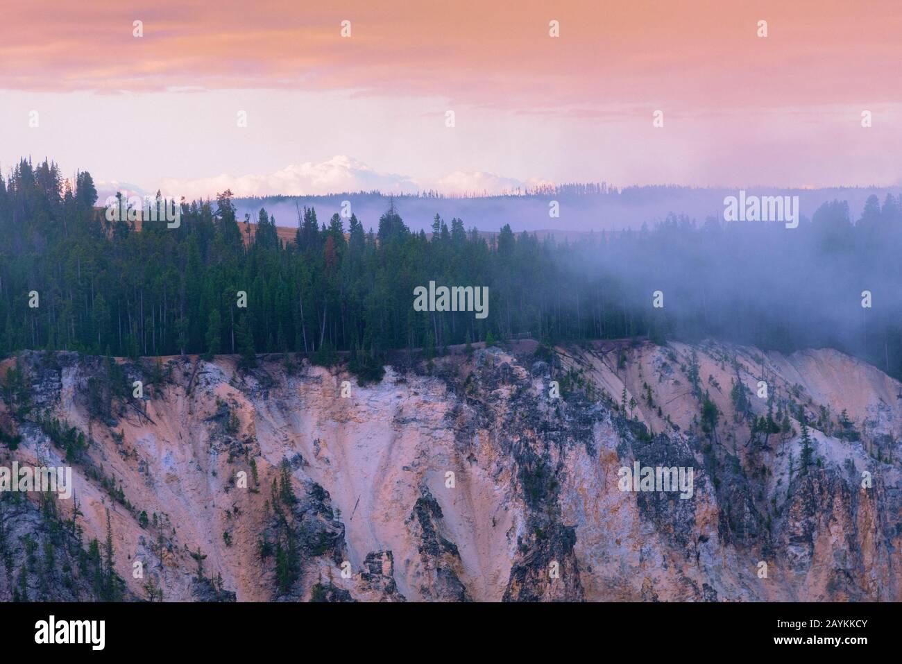 Puesta de sol sobre bosque brumoso en el cielo de montaña bajo el cielo naranja pastel. Foto de stock