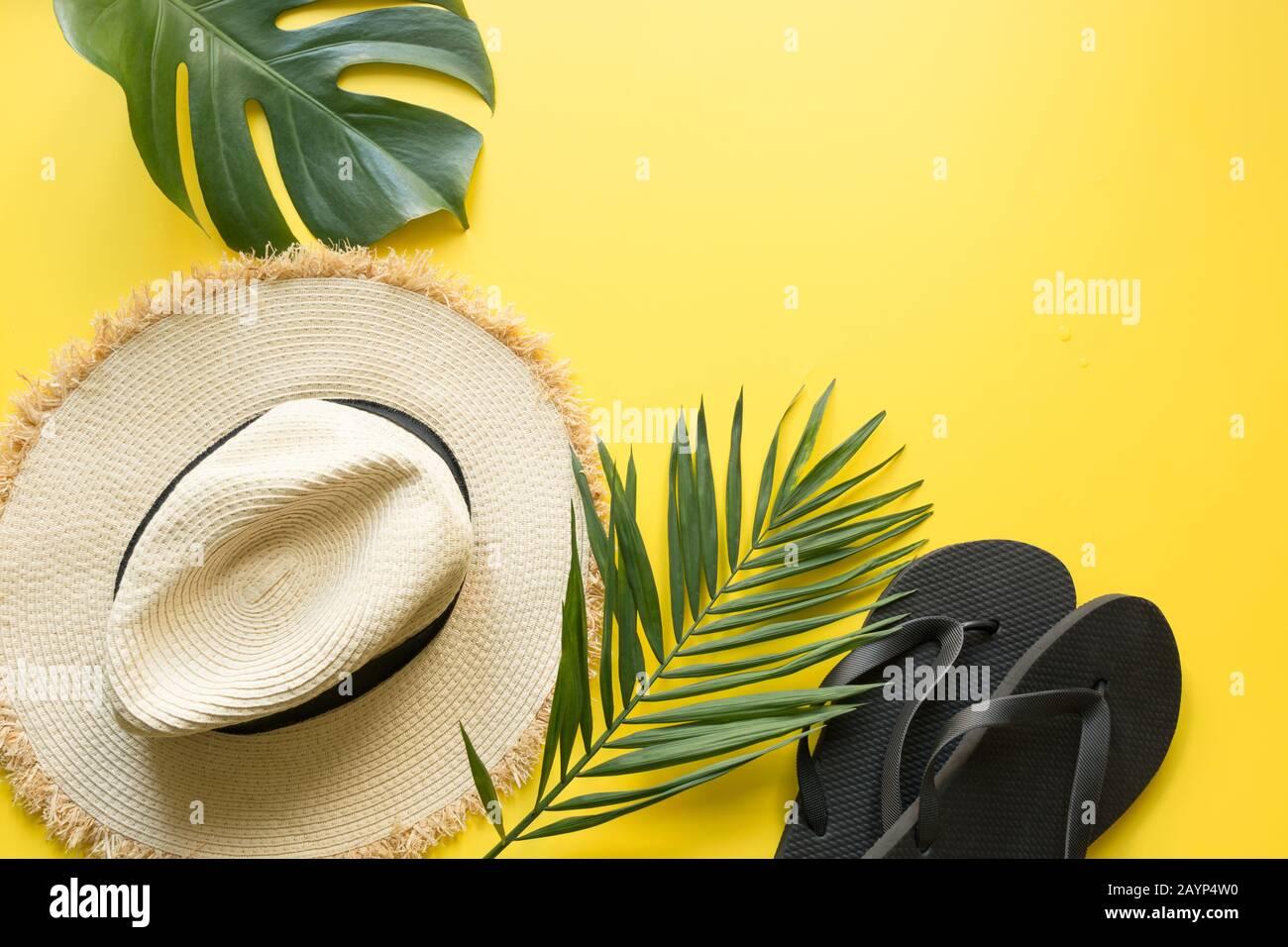 Sombrero de paja de playa, chanclas y hojas de monstera. Fondo de vacaciones de verano con accesorios en amarillo. Vista desde arriba, plano. Espacio para texto. Foto de stock