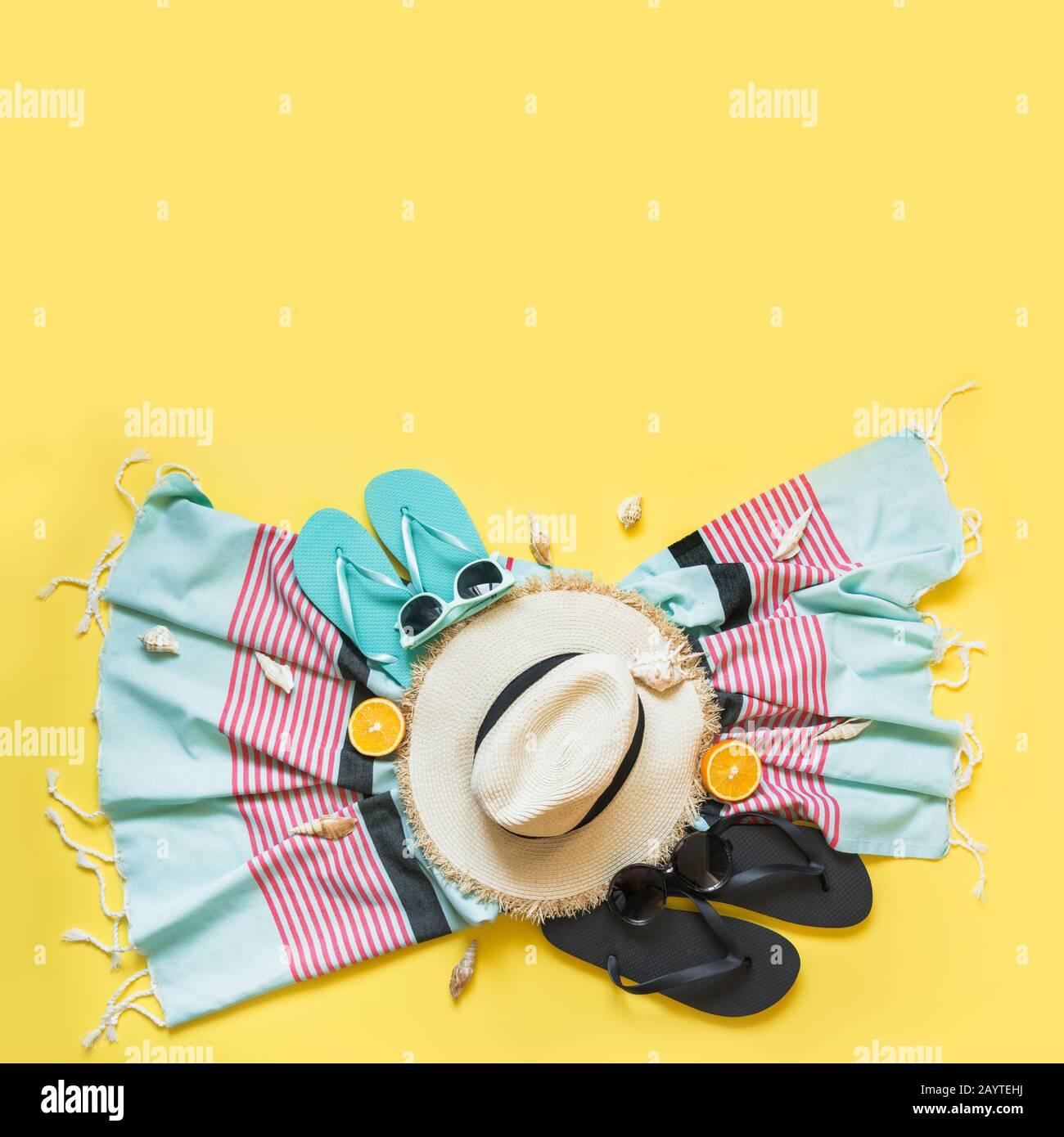 Conjunto para vacaciones tropicales en la playa, sombrero de paja, toalla, gafas de sol en amarillo. Concepto de verano. Vista superior. Espacio para texto. Foto de stock