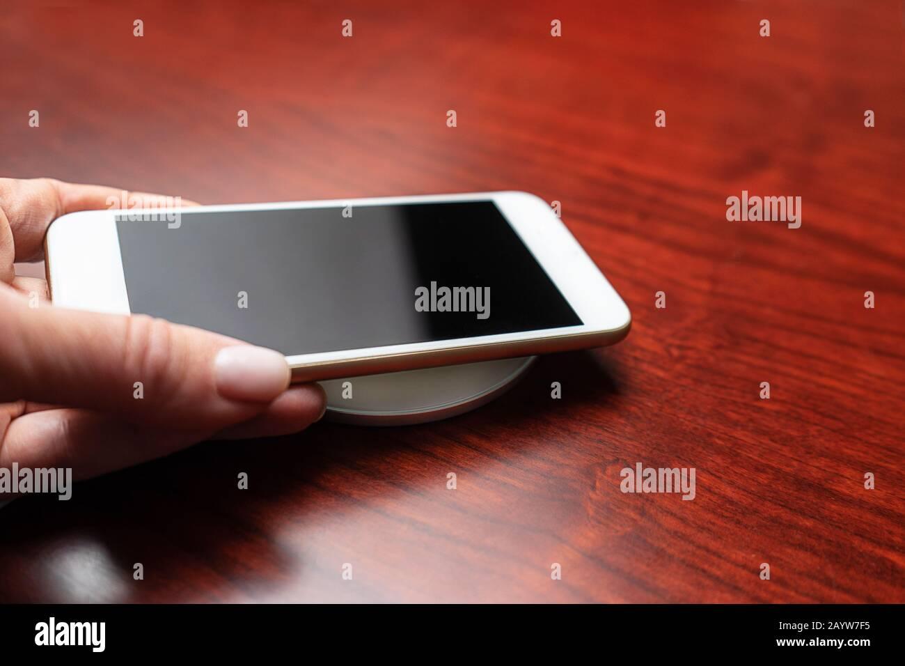 Con la mano se puede guardar un smartphone móvil para cargarlo de forma inalámbrica compartiendo la batería a través del dispositivo. Tecnología de carga. Uso Compartido De Carga De Dispositivos Técnicos. Nueva tecnología, transferencia de electricidad sin cables. Primer plano. Foto de stock