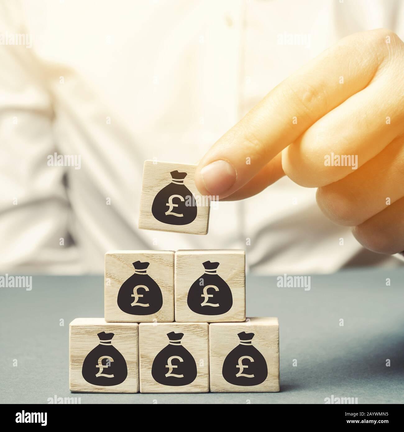 Businessman pone bloques de madera con la imagen del dinero. Concepto de negocio. Gestión de beneficios, finanzas y presupuesto. Planificación. Distribución de fondos. Capi Foto de stock