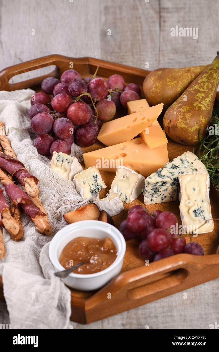 Antipasto. Plato con grissini crujiente envuelto en tocino seco, rebanadas de queso brie, camembert, queso azul y uva moscatel con fruta Foto de stock