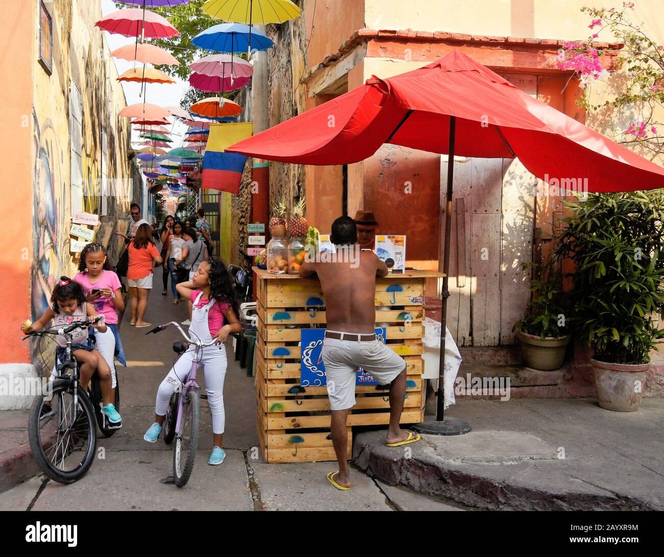 El arte callejero y las sombrillas proporcionan color y sombra en Callejon Angosto en Getsemani, Cartagena, Colombia Foto de stock