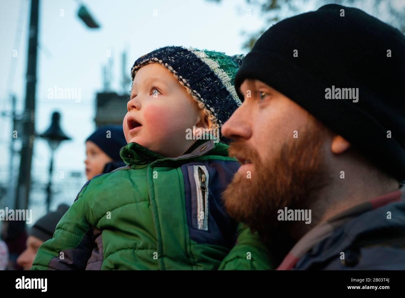 Un padre y un hijo viendo un árbol de Navidad iluminando. Foto de stock