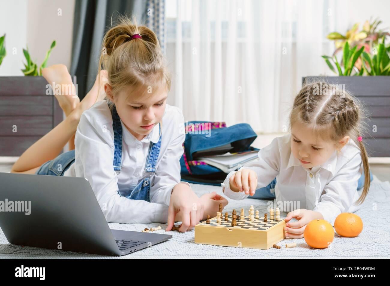 Dos hermosas hermanas jugando ajedrez en un Tablet PC. Foto de stock