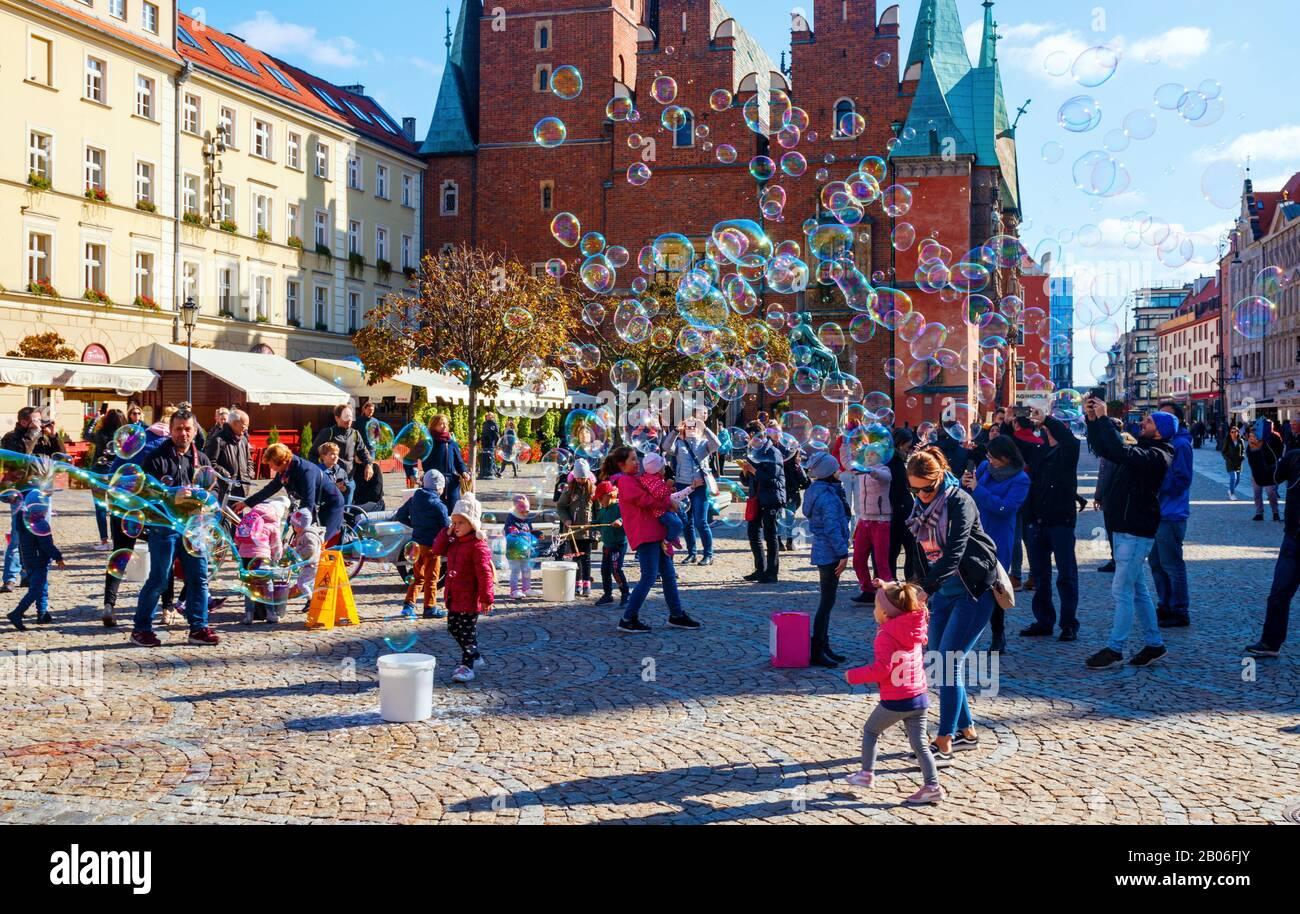 Niños jugando y divertirse con burbujas de jabón en la antigua Plaza del mercado con el ayuntamiento en el fondo en un día soleado. Wroclaw, Polonia. Foto de stock