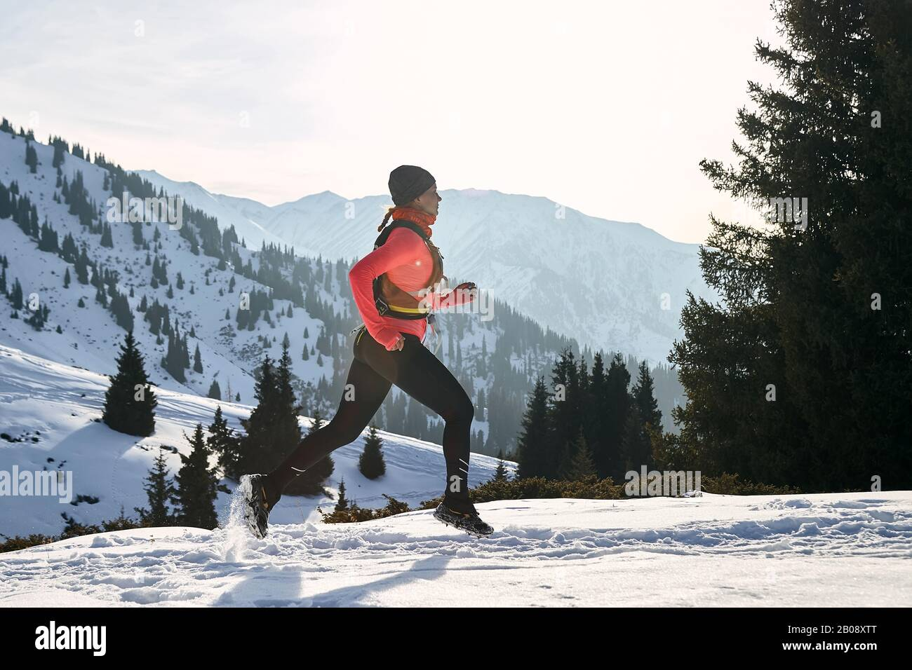 Corredor en chaqueta rosa mujer corriendo en invierno montaña camino en la nieve. Foto de stock